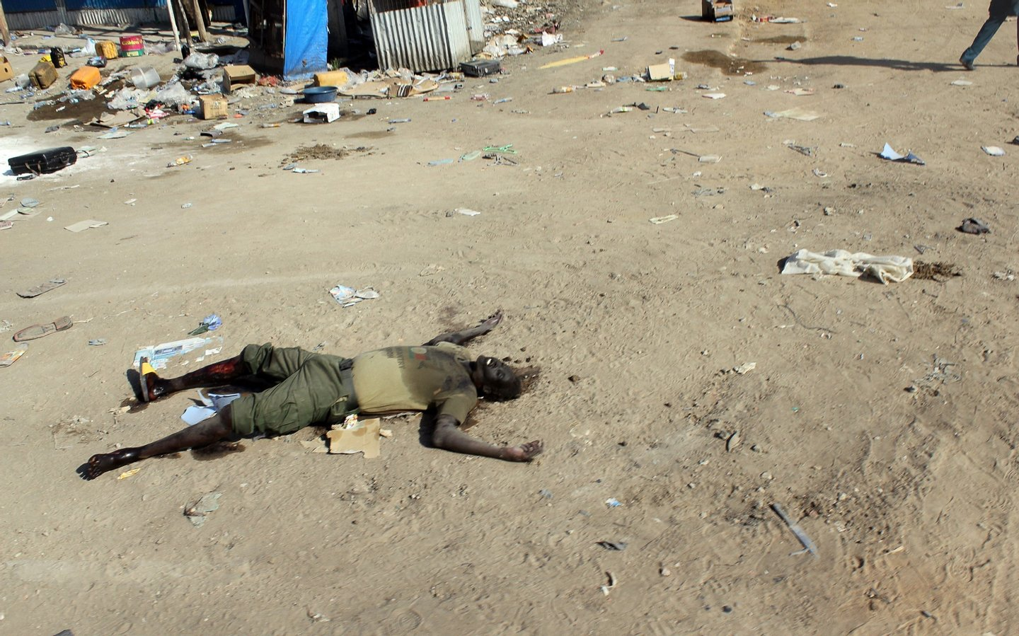 The body of a man claimed to be a rebel lies on the ground in the market in the centre of Bor, some 200 kilometres (125 miles) north of the capital Juba, on December 25, 2013. South Sudan's army stormed the rebel-held town of Bor on December 24, sending insurgents fleeing nearly a week after they captured the state capital of South Sudan's power-key eastern state of Jonglei. AFP PHOTO / WAAKHE SIMON WUDU (Photo credit should read WAAKHE SIMON WUDU/AFP/Getty Images)