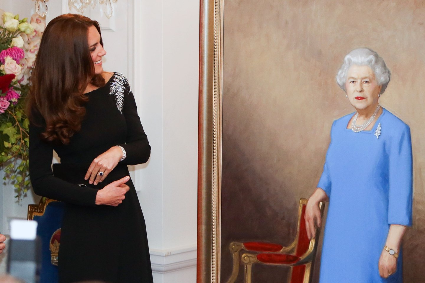 WELLINGTON, NEW ZEALAND - APRIL 10: Catherine, Duchess of Cambridge inspects a portrait of Queen Elizabeth II, painted by New Zealand artist Nick Cuthell and unveiled during a state reception at Government House on April 10, 2014 in Wellington, New Zealand. The Duke and Duchess of Cambridge are on a three-week tour of Australia and New Zealand, the first official trip overseas with their son, Prince George of Cambridge. (Photo by Hagen Hopkins/Getty Images)