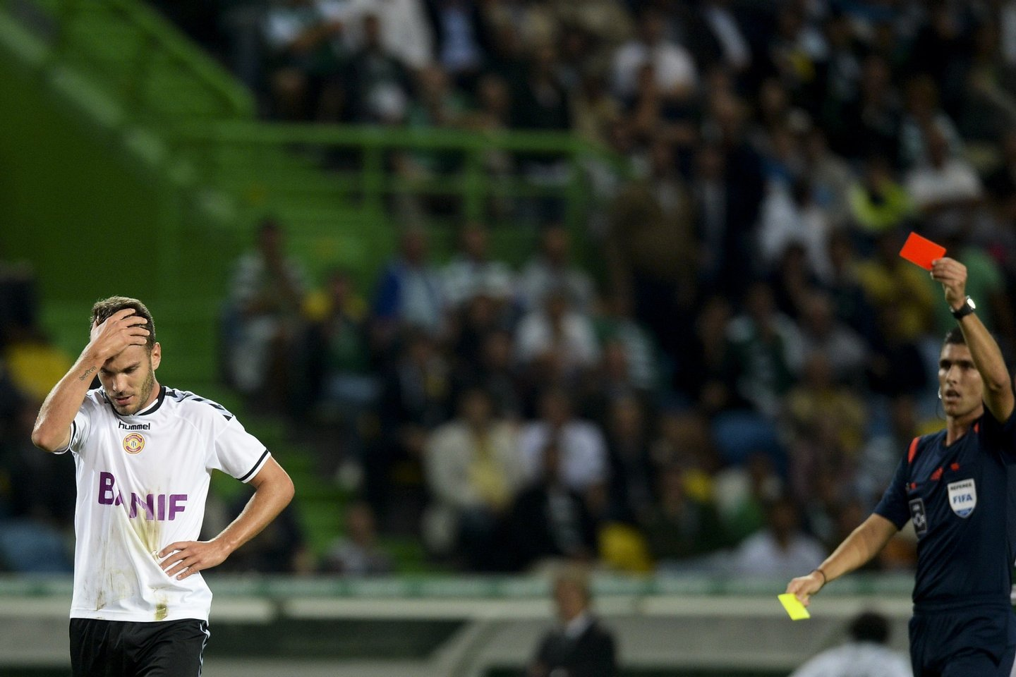 Nacional's defender Nuno Sequeira (L) is shown a red card by referee Fabio Verissimo (R) during the Portuguese Liga football match Sporting CP vs CD Nacional at the Alvalade stadium in Lisbon on September 21, 2015. AFP PHOTO/ PATRICIA DE MELO MOREIRA (Photo credit should read PATRICIA DE MELO MOREIRA/AFP/Getty Images)