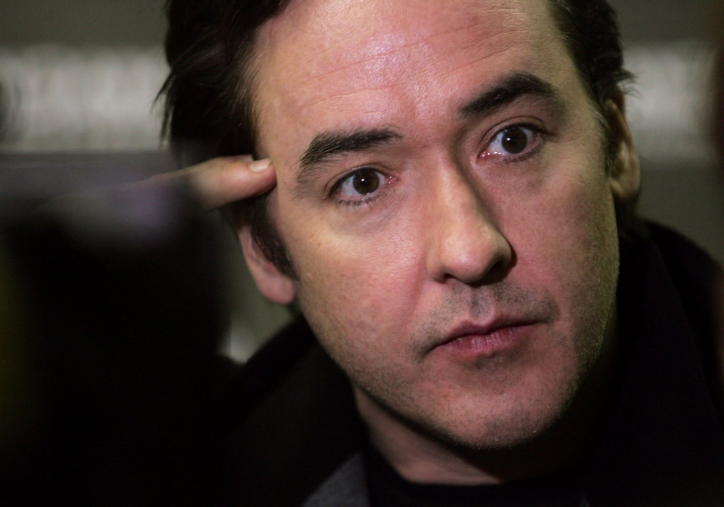 """PARK CITY, UT - JANUARY 20: Actros John Cusack talks to the media during arrivals at the """"Grace Is Gone"""" premiere held at the Racquet Club during the 2007 Sundance Film Festival on January 20, 2007 in Park City, Utah. (Photo by Peter Kramer/Getty Images)"""