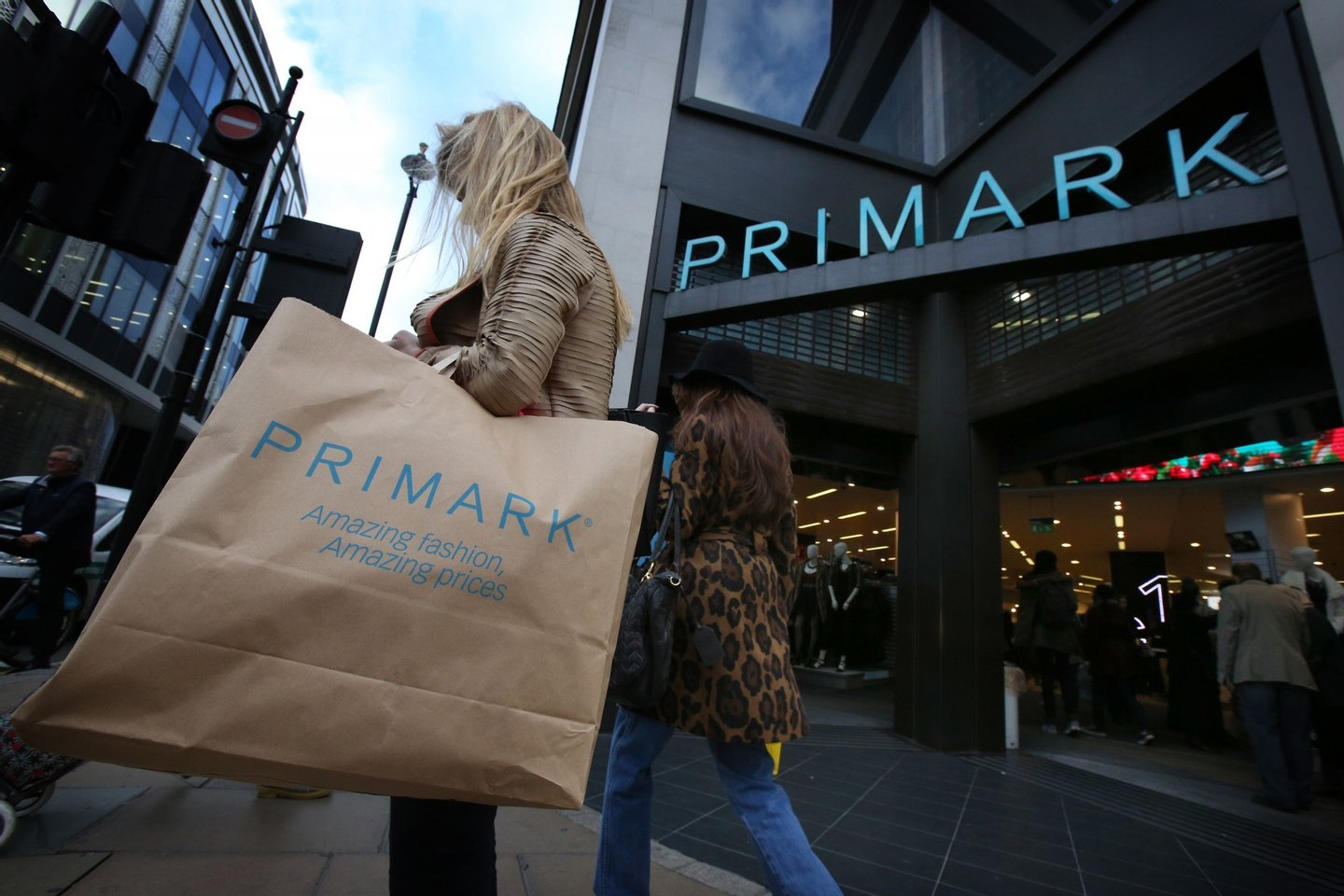 LONDON, ENGLAND - NOVEMBER 05:  A customer waits with her purchases outside Primark's flagship store on Oxford Street on November 5, 2014 in London, England. Retail giant Marks and Spencer have shown a continued decline in clothes sales as budget fashion chain Primark has delivered a 16% increase in its sales.  (Photo by Peter Macdiarmid/Getty Images)