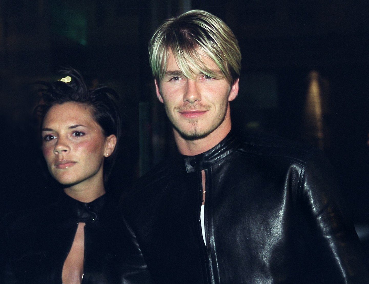 """Spice Girls Victoria Adams (L) arrives with her husband, Manchester United and England star David Beckham (R), to a Versace star-studded reception hosted by Donatella Versace in London late Friday 11 June 1999. The reception comes after the Versace """"Diamonds are forever"""" charity fashion event 09 June which raised funds for three charities including the Prince's Foundation for architecture and the environment. (Photo credit should read SINEAD LYNCH/AFP/Getty Images)"""