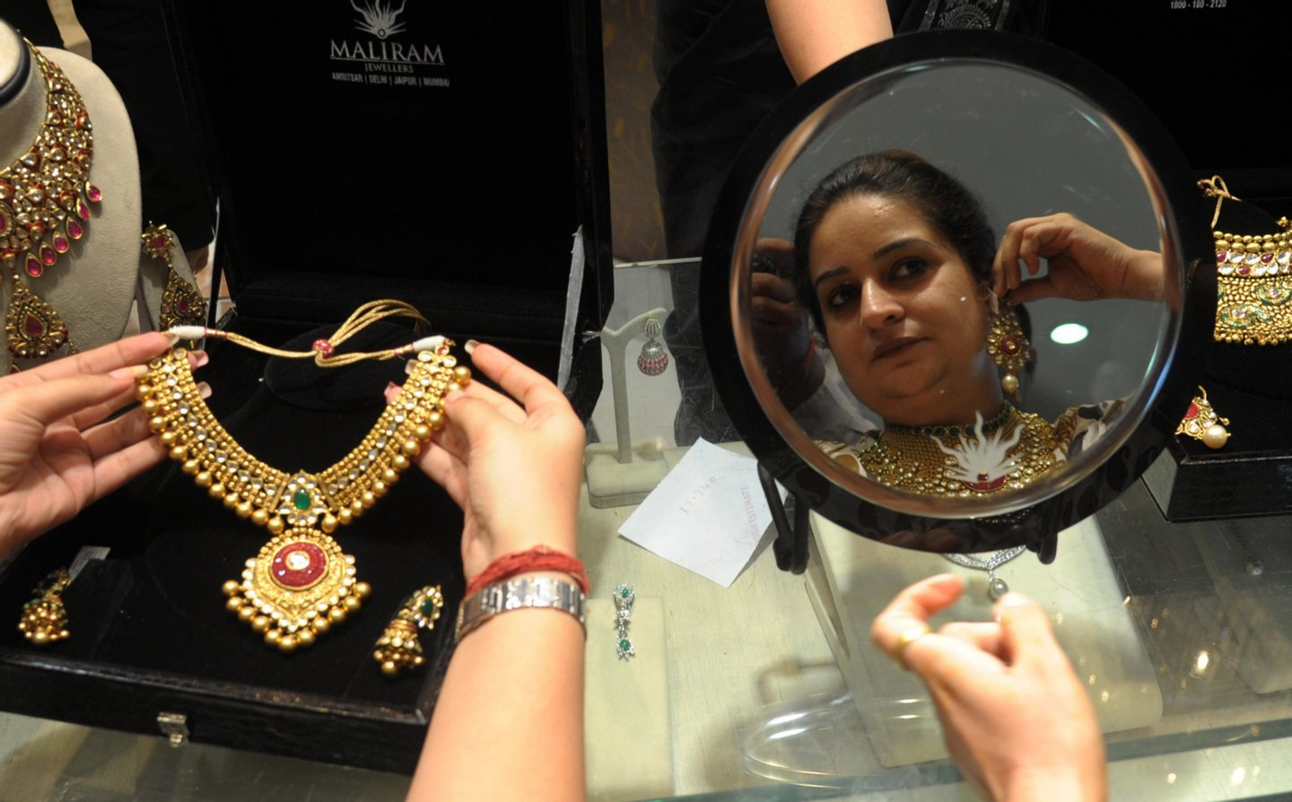 Indian shoppers try on gold jewellery at a jewellery store on Dhanteras in Amritsar on October 21, 2014. Dhanteras, which happens two days before the Hindu festival Diwali, is seen as an auspicious day to make purchases. AFP PHOTO/NARINDER NANU (Photo credit should read NARINDER NANU/AFP/Getty Images)