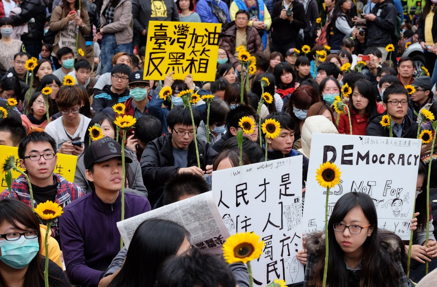 Students display flowers and placards during ongoing protests by thousands of people outside the parliament in Taipei on March 22, 2014. Student protesters occupying Taiwan's legislature to stop the government from ratifying a contentious trade pact with China on March 21 called on the public to surround the ruling party's offices after their ultimatum was ignored. AFP PHOTO / Sam Yeh (Photo credit should read SAM YEH/AFP/Getty Images)