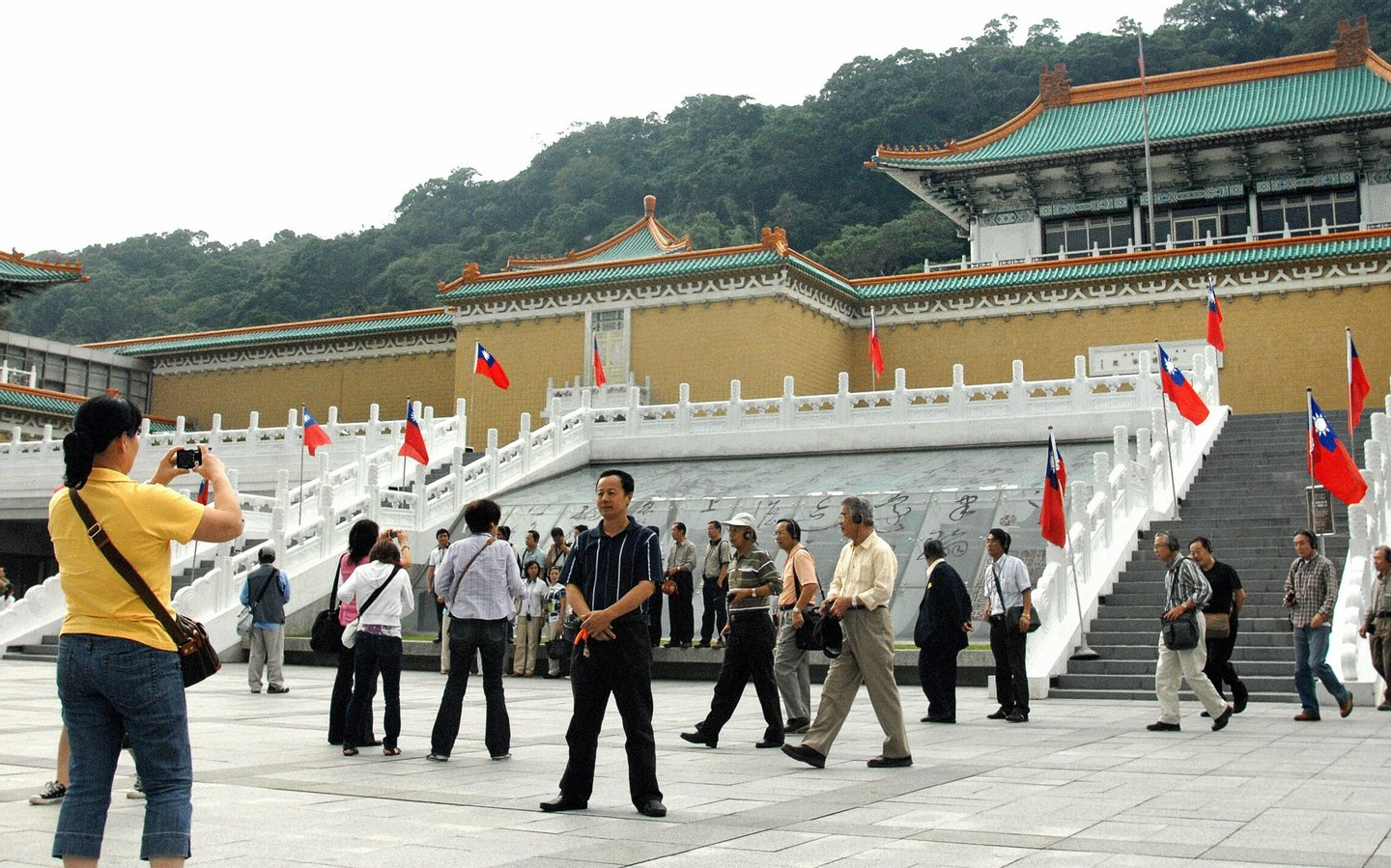 TO GO WITH: FINANCE-ECONOMY-TAIWAN-CHINA-TOURISM by Amber Wang Chinese tourists take pictures outside Taiwan's popular sight-seeing spot the National Palace Museum in Taipei on October 26, 2008. Taiwanese authorities were counting on the mainland visitors to bring in 60 billion Taiwan dollars (1.87 billion US) annually in a major boost to its tourism but despite the rapprochement between the two sides, fewer than 300 Chinese visitors came to the island on average every day since July. AFP PHOTO/PATRICK LIN (Photo credit should read PATRICK LIN/AFP/Getty Images)