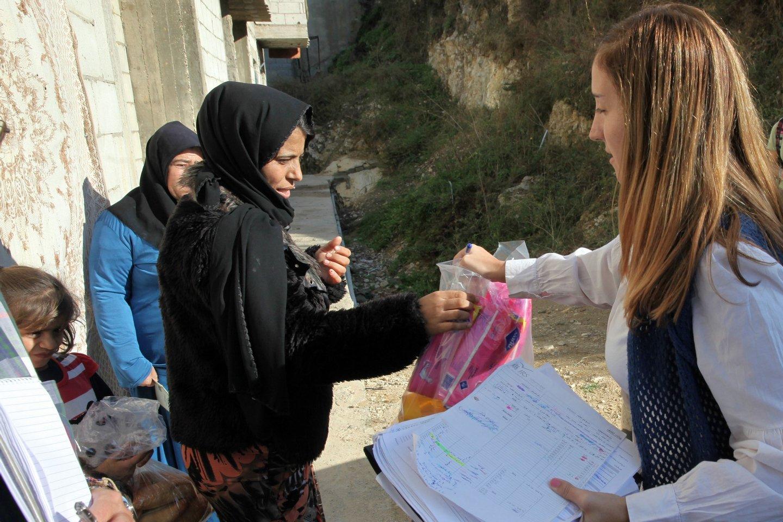 Shamra (C) tem 35 anos, os quatro últimos já celebrados no Líbano, recebe produtos de higiene de Tania, também ela refugiada. (19 de novembro de 2015) NUNO VEIGA/LUSA