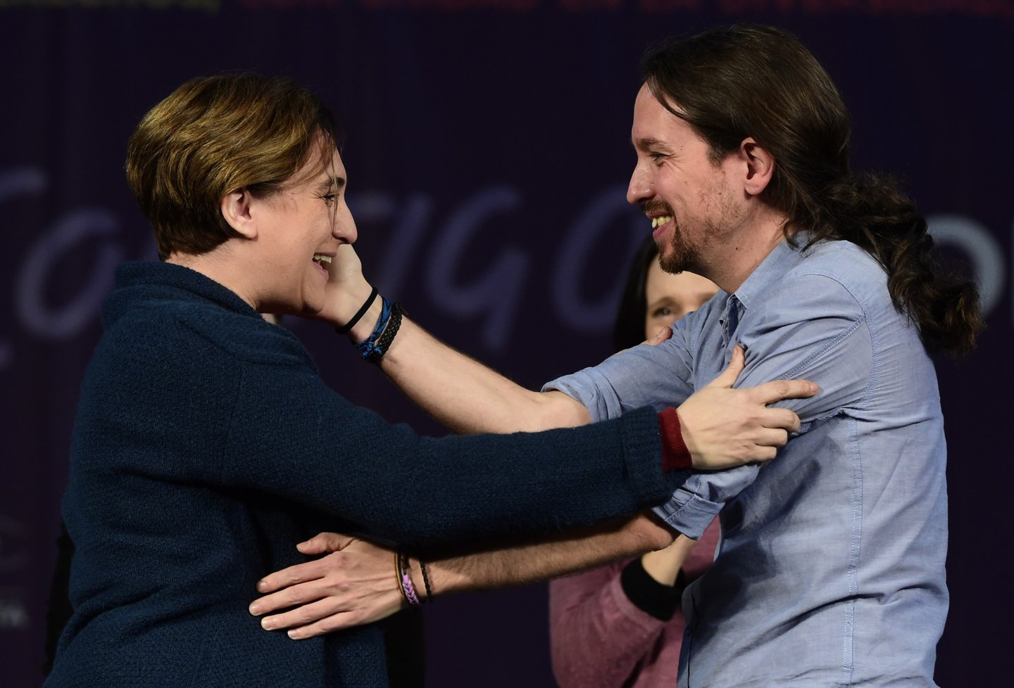 Leader of left wing party Podemos and candidate for the upcoming December 20 general election, Pablo Iglesias (R) hugs Barcelona's Mayor Ada Colau during a campaign meeting in Madrid on December 13, 2015. Public over corruption across the political spectrum, as well as companies, unions, banks, celebrities, and even royalty could cost Spain's traditional parties dearly in upcoming elections as sky-high unemployment and austerity has seen the emergence of two new parties -- the anti-austerity Podemos and centrist Ciudadanos -- both threatening to the two-party monopoly at the polls says sociologist Jose Pablo Ferrandiz of polling institute Metroscopia. AFP PHOTO / JAVIER SORIANO / AFP / JAVIER SORIANO (Photo credit should read JAVIER SORIANO/AFP/Getty Images)