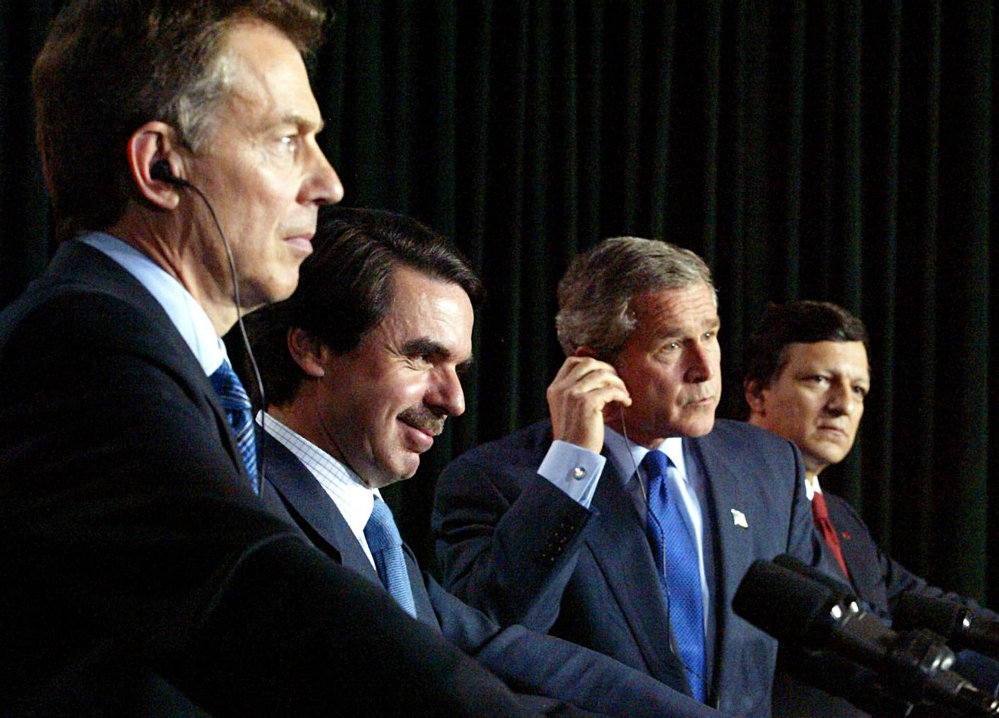 (L-R) Britain's Prime Minister Tony Blair, Spanish Prime Minister Jose Maria Aznar, US President George W. Bush and Portuguese Prime Minister Jose Manuel Durao Barosso listen at their joint press conference following meetings to discuss prospects for resolving the Iraq situation peacefully with diplomacy in final pursuit of a United Nations resolution 16 March, 2003, at Lajes Field on the island of Terceira in the Azores, Portugal. The four leaders, all facing anti-war opposition of varying degrees at home are the sponsors of a UN resolution that would set the stage for war on Iraq. (Photo by Luke FRAZZA/AFP/Getty Images)