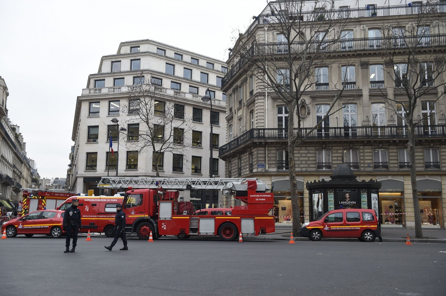"""French police officers stand guard next to fire trucks parked near the Ritz Hotel in Paris after a fire broke out at the landmark hotel on January 19, 2016. A major fire broke out at the landmark Paris Ritz hotel, which is closed for renovations, the fire service said. The blaze is on the """"top floor of the building and the roof"""", a fire service spokesman said. AFP PHOTO / LIONEL BONAVENTURE / AFP / LIONEL BONAVENTURE (Photo credit should read LIONEL BONAVENTURE/AFP/Getty Images)"""