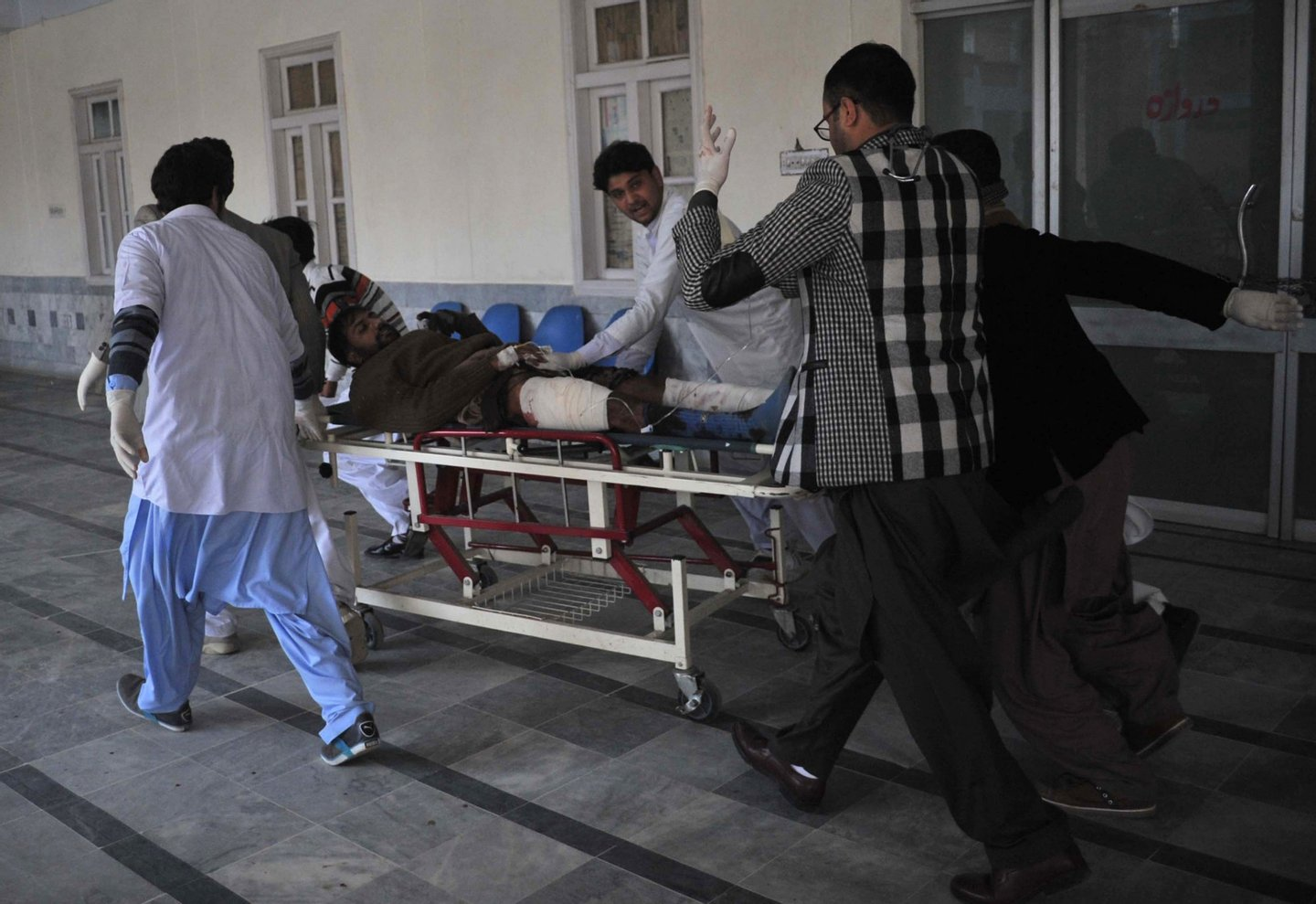 Pakistani rescuers shift an injured man at a hospital following an attack by gunmen at Bacha Khan university in Charsadda, about 50 kilometres from Peshawar, on January 20, 2016. At least 21 people died in an armed assault on a university in Pakistan on January 20, where witnesses reported two large explosions as security forces moved in under dense fog to halt the bloodshed. AFP PHOTO /Hasham AHMED / AFP / HASHAM AHMED (Photo credit should read HASHAM AHMED/AFP/Getty Images)