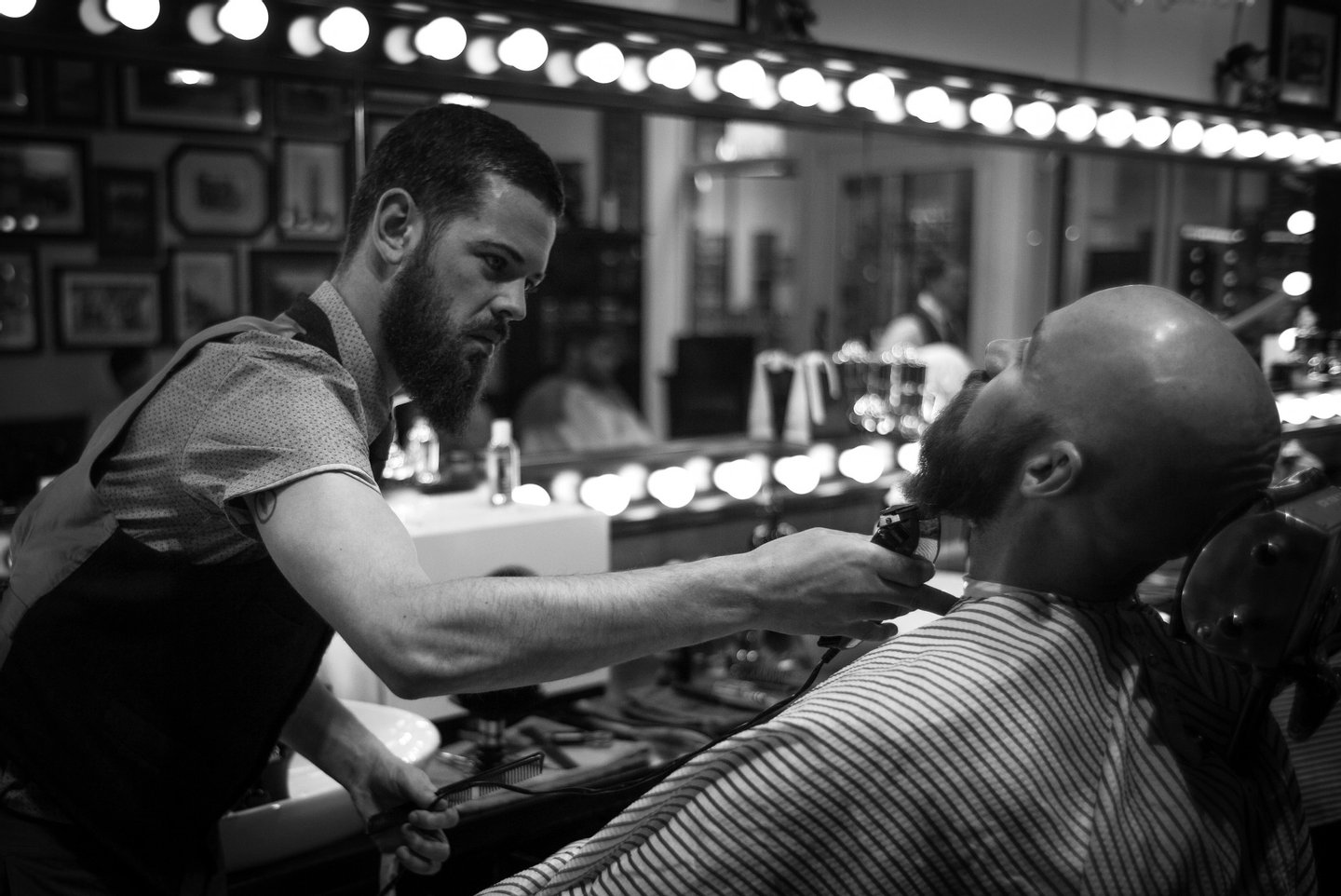MANCHESTER, ENGLAND - APRIL 29: (EDITORS NOTE: This image has been converted to black and white. Colour version available upon request.) Barber Ricky Trim wet shaves a customer in Manchester's Barber Barber, a 'gentleman's saloon' style male barber shop, on April 29, 2015 in Manchester, England. According to owner Johnny the Baba, Barber Barber is the UK's finest barber shop. The shop for 'gentleman and scoundrels' takes a traditional approach to male grooming, and offers services such as wet shaving, beard scultping and highly skilled hair styling. The shop also offers complimentary drinks and cigars to it's customers and operates a 'gentlemen only' door policy. (Photo by Christopher Furlong/Getty Images)