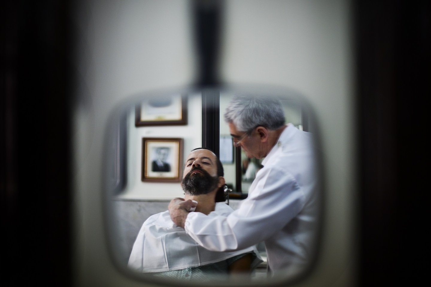 "A barber shaves the beard of a customer at the barber shop ""Barbearia Campos"", open since 1886, in Lisbon on July 16, 2013. AFP PHOTO/ PATRICIA DE MELO MOREIRA (Photo credit should read PATRICIA DE MELO MOREIRA/AFP/Getty Images)"