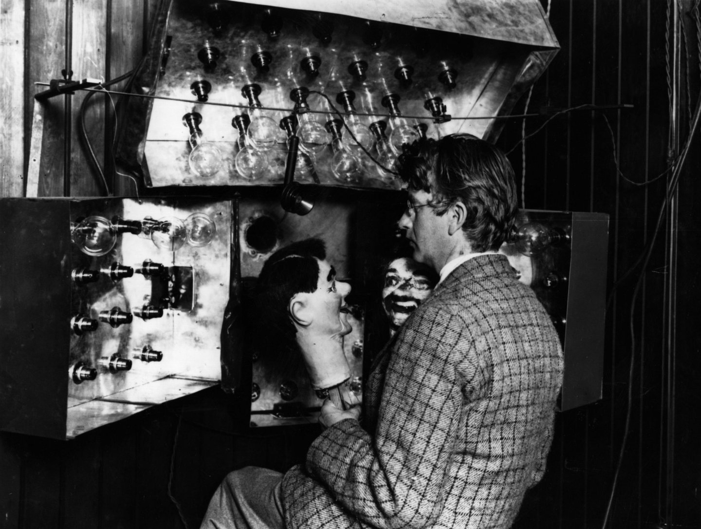Scottish electrical engineer and television pioneer John Logie Baird (1888 - 1946) demonstrating his new invention the television with the aid of two ventriloquist's dummies. Baird was born in Helensburgh and studied at Glasgow University. Baird worked as an engineer at Clyde Valley Electric Power Company but had to retire due to ill health. He used his time to conduct experimental research into the transmission of images and gave a successful public display of his television system in London on 27th January 1926. In 1929 his mechanically scanned system was adopted by the BBC and he provided an improved system five years later. Baird also helped pioneer colour television and stereophonic sound. (Photo by Topical Press Agency/Getty Images)