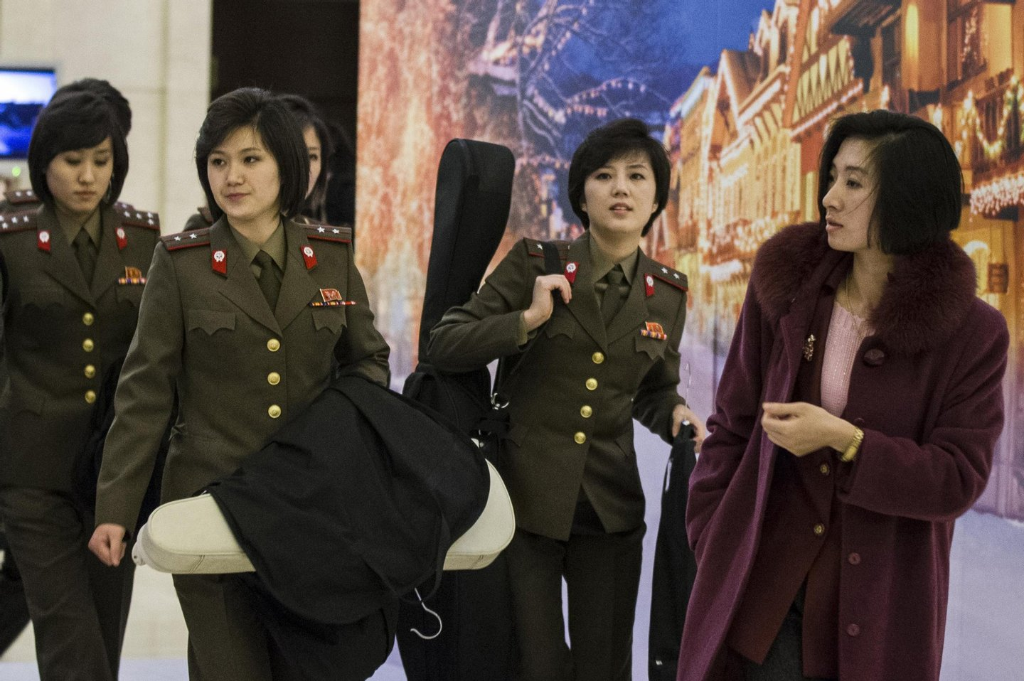 This picture taken on December 10, 2015 shows members of North Korea's Moranbong band walking out of their hotel in Beijing. North Korea's premier pop group, the all-girl Moranbong band formed by leader Kim Jong-Un, is electrifying audiences in China in shows aimed at harmonising out-of-tune ties between the traditional allies, reports and the venue said on December 9 -- but tickets are not available to the public. CHINA OUT AFP PHOTO / AFP / STR (Photo credit should read STR/AFP/Getty Images)