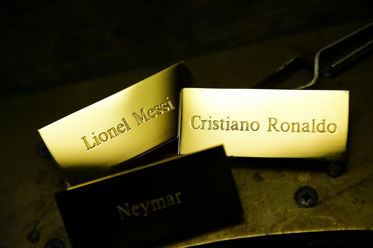 """A picture taken on December 15, 2015 shows three plaques reading, """"Cristiano Ronaldo"""", """"Lionel Messi"""" and """"Neymar"""" at the Mellerio jewellers in Paris, as part of the crafting of the Ballon d'Or 2015 Fifa award. Barcelona's Argentinian forward Lionel Messi, Barcelona's Brazilian forward Neymar and Real Madrid's Portuguese forward Cristiano Ronaldo were shortlisted for the Ballon d'Or 2015, Fifa's annual football award given to the male player considered to have performed the best in the previous calendar year, and that will be awarded on January 11, 2016 during a gala event in Zurich. / AFP / FRANCK FIFE (Photo credit should read FRANCK FIFE/AFP/Getty Images)"""
