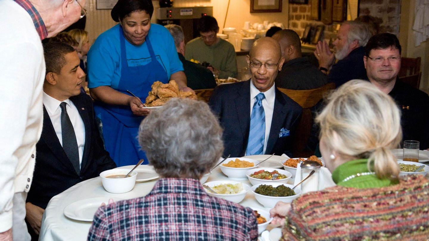A waitress brings a plate of fried chicken to a table where US President Barack Obama speaks with patrons while eating lunch at Mrs. Wilkes' Dining Room in Savannah, Georgia, March 2, 2010. Obama traveled to the area for the next stop of the White House to Main Street Tour, where he visits local businesses and speaks about the economy. AFP PHOTO / Saul LOEB (Photo credit should read SAUL LOEB/AFP/Getty Images)