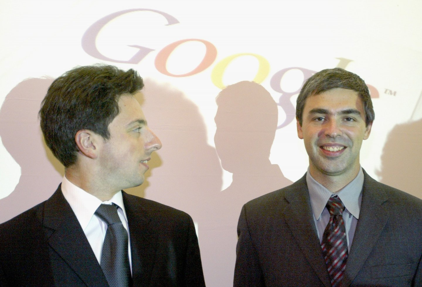 """FRANKFURT, GERMANY - OCTOBER 7: Google founders Sergey Brin (L) and Larry Page (R) joke prior to a news conference during the opening of the Frankfurt bookfair on October 7, 2004 in Frankfurt, Germany. The Frankfurt Bookfair is the world's largest event of it's type and this year's focal theme """"Literature of Arabia"""" will run until October 10, 2004. (Photo by Ralph Orlowski/Getty Images)"""