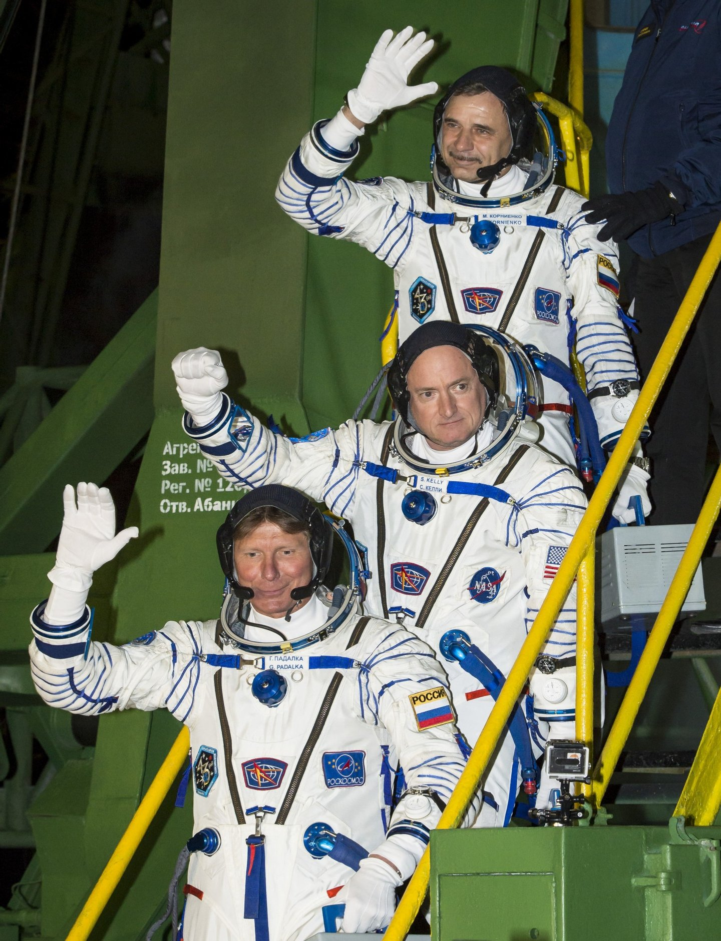 Expedition 43 Russian Cosmonaut Mikhail Kornienko of the Russian Federal Space Agency (Roscosmos), top, NASA Astronaut Scott Kelly, center, and Russian Cosmonaut Gennady Padalka of Roscosmos wave farewell as they board the Soyuz TMA-16M spacecraft ahead of their launch to the International Space Station, Friday, March 27, 2015 in Baikonor, Kazakhstan. As the one-year crew, Kelly and Kornienko will return to Earth on Soyuz TMA-18M in March 2016. Photo Credit (NASA/Bill Ingalls)