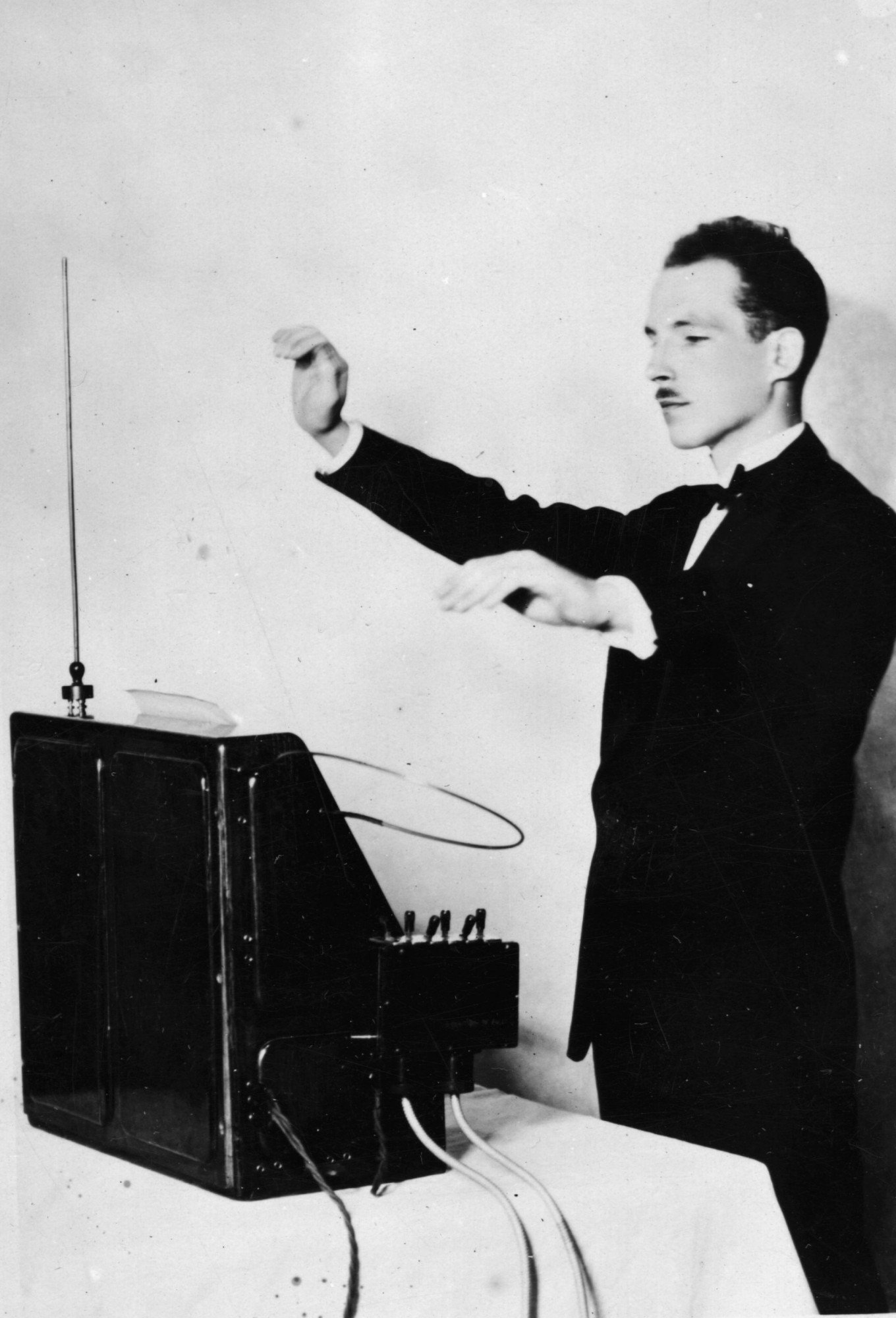 12th December 1927: Professor Leon Theremin demonstrating his theremin. The theremin was the world's first electronic musical instrument. It is played without actually touching any part of the instrument. Film scores of the 40s and 50s used the instrument to eerie effect and it makes a famous appearance in the chorus of the Beach Boys hit 'Good Vibrations'. (Photo by Topical Press Agency/Getty Images)