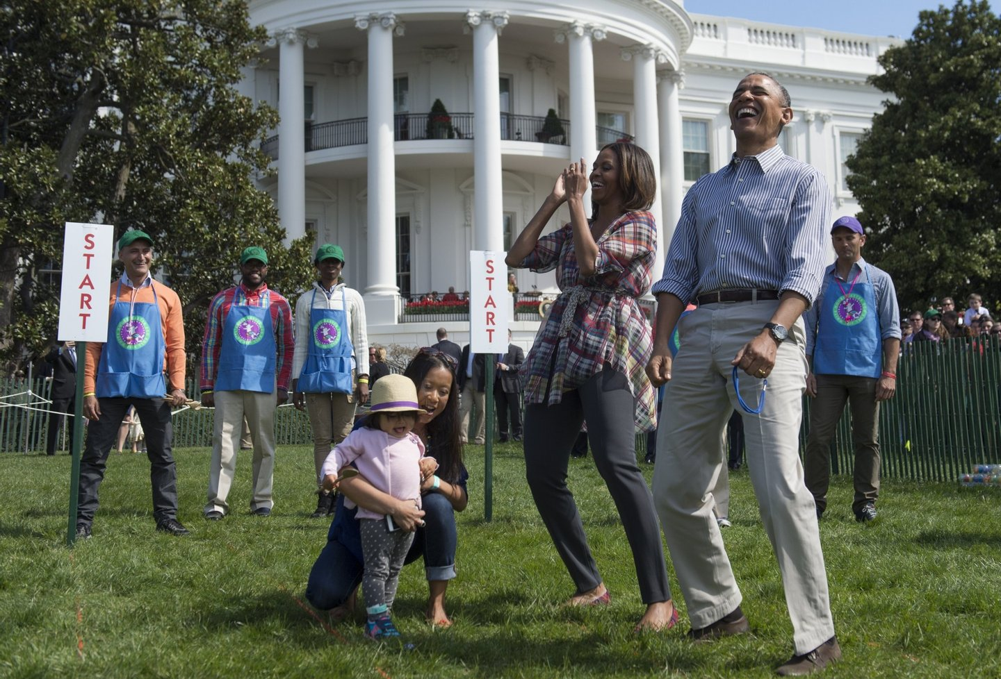 "US President Barack Obama and First Lady Michelle Obama react to a child rolling an Easter egg during the annual White House Easter Egg Roll on the South Lawn of the White House in Washington, DC, April 21, 2014. The 126th annual White House Easter Egg Roll, the largest annual public event at the White House with more than 30,000 attendees expected, features live music, sports courts, cooking stations, storytelling and Easter egg rolling, with the theme, ""Hop into Healthy, Swing into Shape."" AFP PHOTO / Saul LOEB (Photo credit should read SAUL LOEB/AFP/Getty Images)"