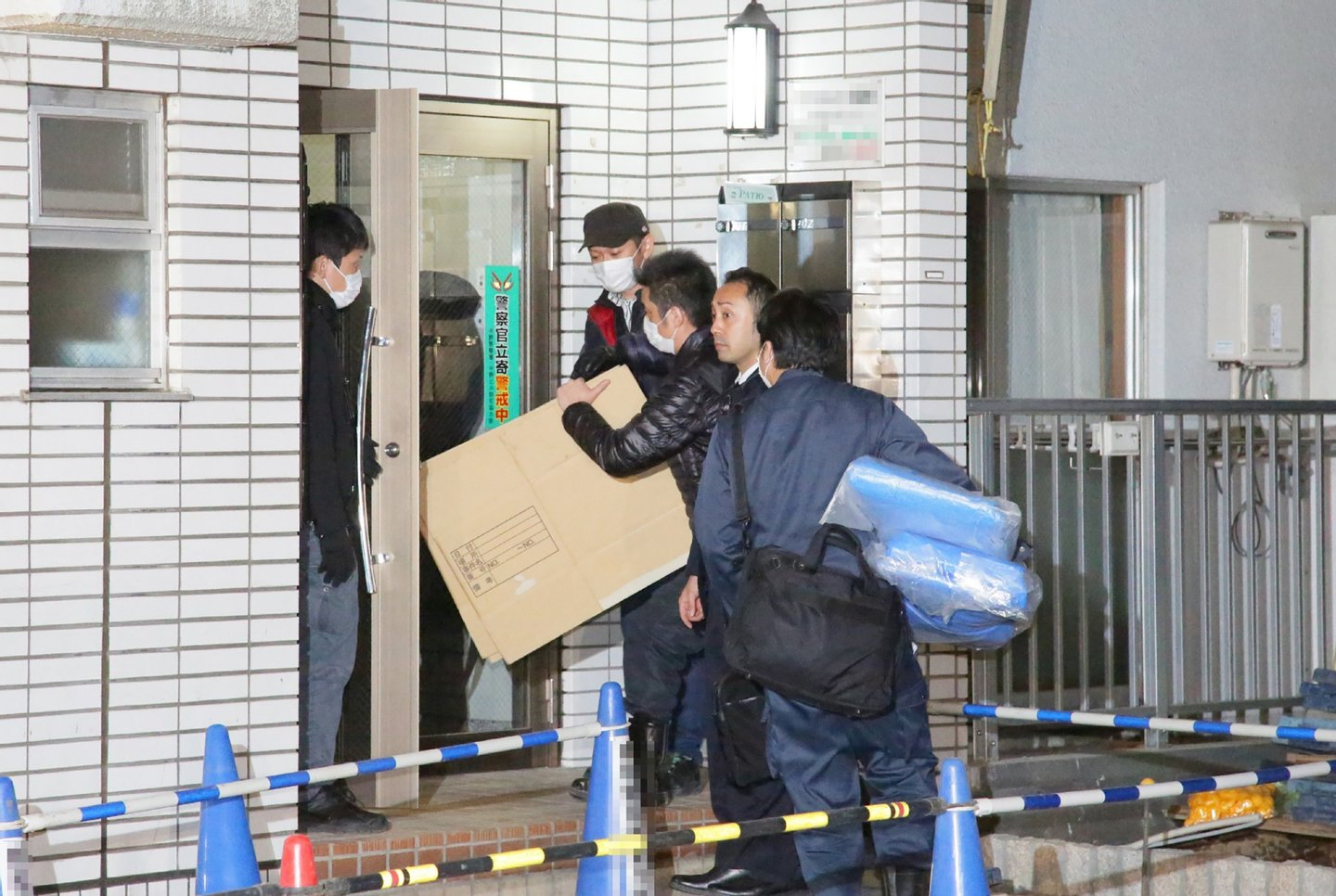 Police investigators enter an the apartment of the suspect believed to be lived with a girl in Tokyo on March 28, 2016. A Japanese girl who vanished two years ago has returned home after escaping from the apartment of the university student who had held her captive, police and local media said March 28. / AFP / JIJI PRESS / JIJI PRESS (Photo credit should read JIJI PRESS/AFP/Getty Images)