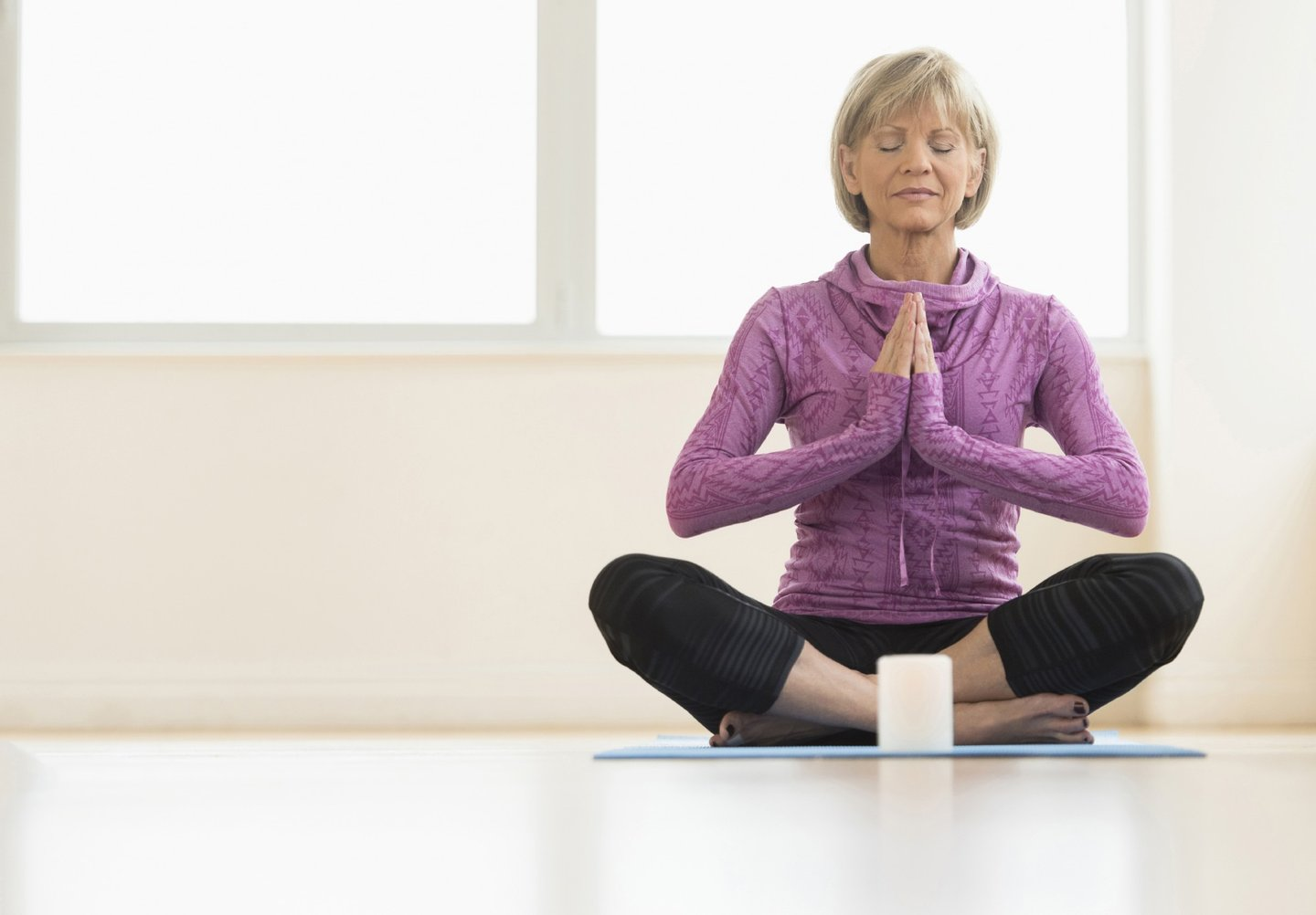 50s, 55-59 Years, Adult, Aging Process, Bangs, Blond Hair, Body Care, Body Conscious, Candle, Casual, Caucasian, Concentration, Cross-Legged, Day, Exercise Mat, Exercising, Eyes Closed, Female, Floor, Front View, Full Length, Hands Clasped, Healthy Lifestyle, Home Interior, Horizontal, Indoors, Leisure Activity, Lifestyles, Mature Adult, Mature Women, Meditating, One Mature Woman Only, One Person, One Woman Only, Only Mature Women, Only Women, People, Posture, Relaxation, Relaxation Exercise, Routine, Selective Focus, Short Hair, Sitting, Spirituality, Wellbeing, Window, Women, Yoga, Zen-Like,