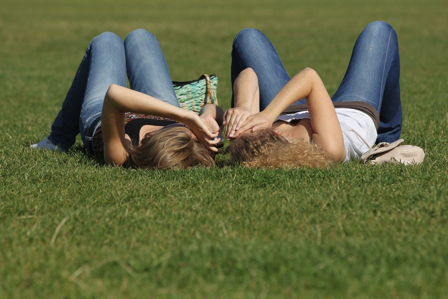 BERLIN, GERMANY - AUGUST 22: Two young women relax ona sunny day on grass near the Reichstag on August 22, 2011 in Berlin, Germany. Germany, which has thus far endured a summer marked by rain and cold, is seeing sunny skies and warm temperatures this week. (Photo by Sean Gallup/Getty Images)