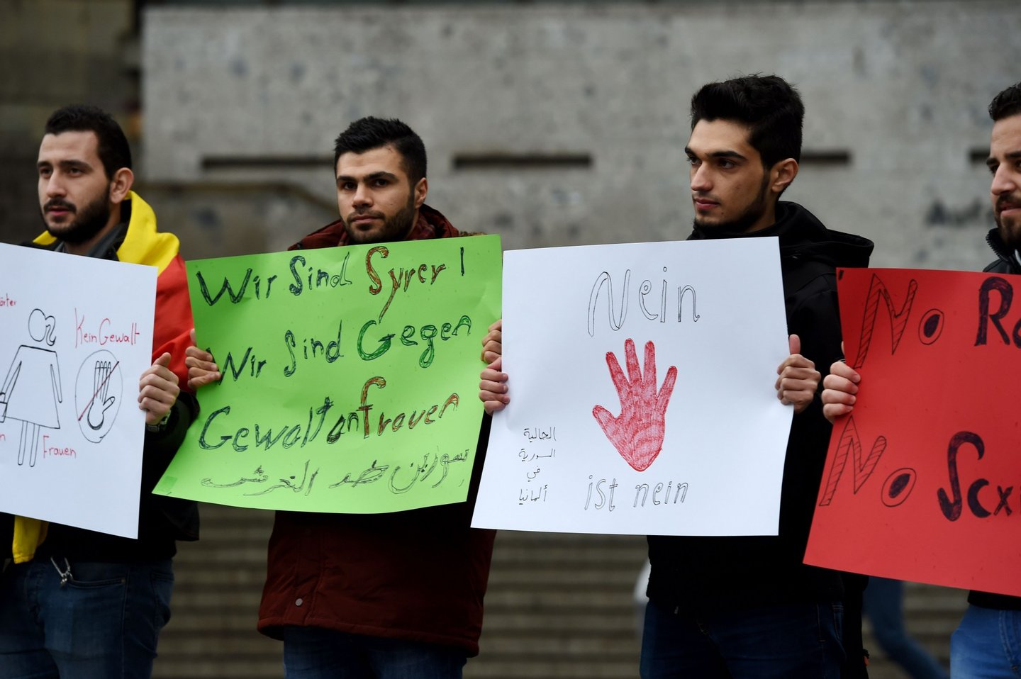 """Refugees from Syria hold a sign reading """"we are syrians-we are against violence against women"""" as they demonstrate against violence at the Cologne main train station in Cologne, western Germany on January 16, 2016 where violence against women were perpetrated on New Year's Eve. / AFP / PATRIK STOLLARZ (Photo credit should read PATRIK STOLLARZ/AFP/Getty Images)"""