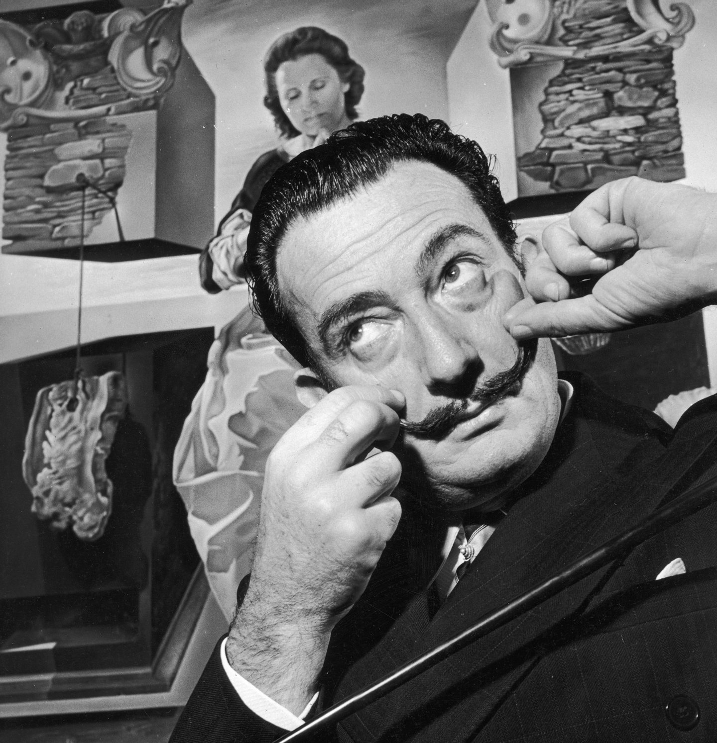 Spanish surrealist artist Salvador Dali (1904 - 1989) in London with one of his paintings entitled 'The Madonna of Port Lligat', December 1951. (Photo by George Konig/Keystone Features/Getty Images)