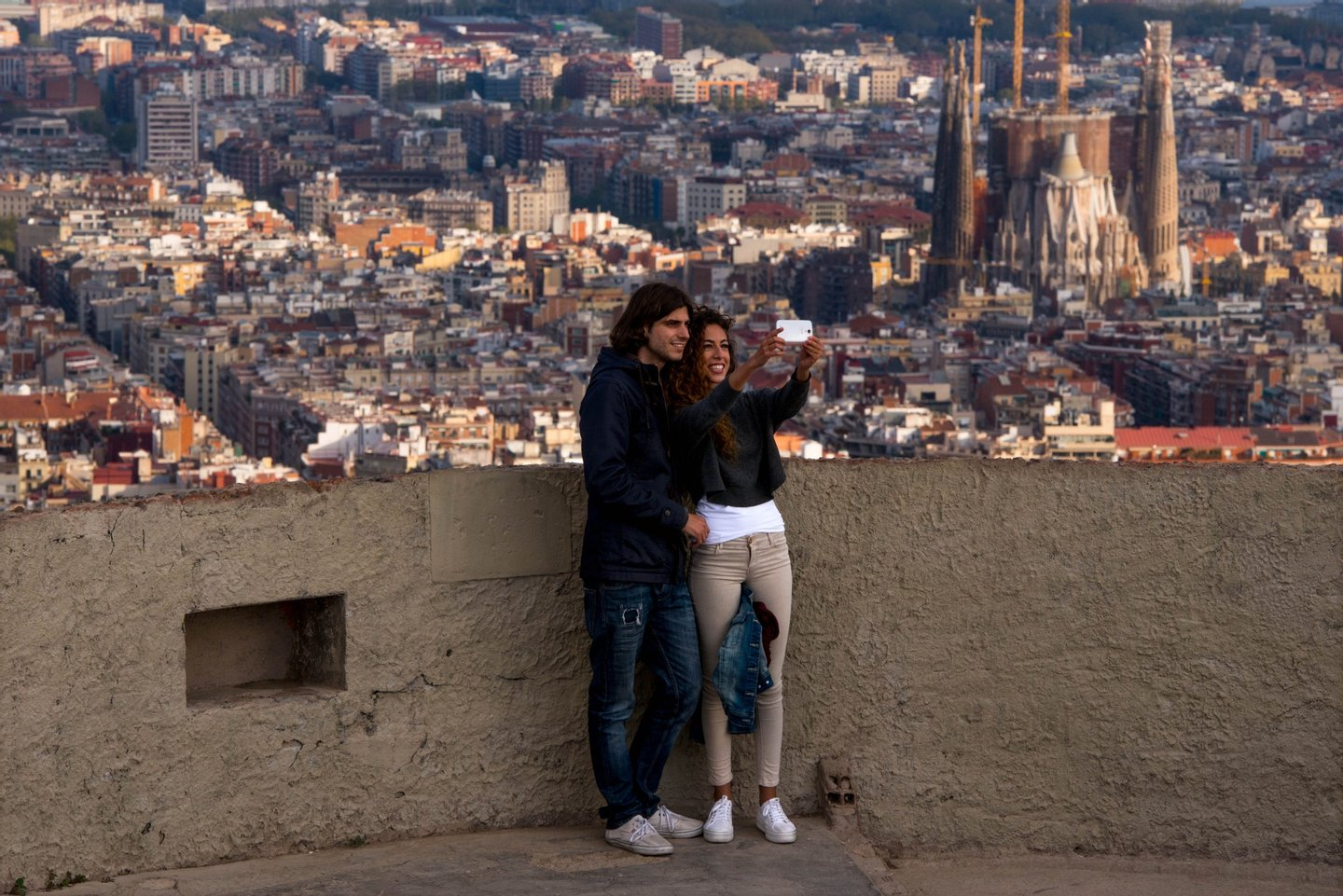 BARCELONA, SPAIN - APRIL 10: A couple take a selfie as they enjoy the views over the city on April 10, 2015 in Barcelona, Spain. Barcelona's city hall has put a regulation in motion that bans large tourist groups visiting Barcelona's most popular market. Barcelona's authorities are debating how to control the number of tourist in the city as an estimated 10 million people are due to visit this year. (Photo by David Ramos/Getty Images)