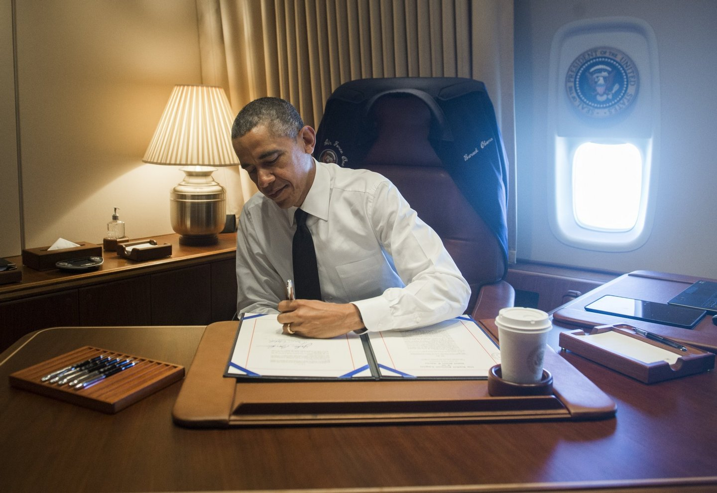 US President Barack Obama signs a bill that will give the Congressional Gold Medal to the Foot Soldiers who Participated in Bloody Sunday in Selma, Alabama, in his office aboard Air Force One as he flies to Alabama on March 7, 2015. Obama is traveling to participate in an event commemorating the 50th anniversary of Bloody Sunday, when civil rights marchers attempting to walk to the Alabama capital of Montgomery to end voting discrimination against African Americans clashed with police. AFP PHOTO / SAUL LOEB (Photo credit should read SAUL LOEB/AFP/Getty Images)