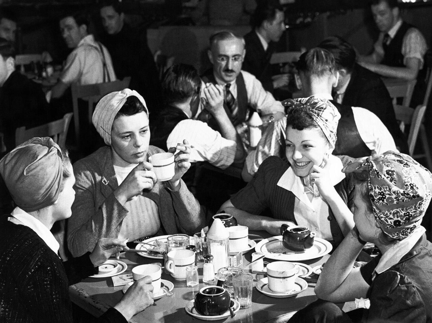 In the foreground, a group of four women, each wearing a working head scarf, are having lunch, smiling and discussing, while other male workers are doing the same in the background of a factory's canteen on the Canadian Home Front during World War II, Canada, 1944. Photo taken during the National Film Board of Canada's production of 'When Do We Eat?'. (Photo by NFB/Getty Images)