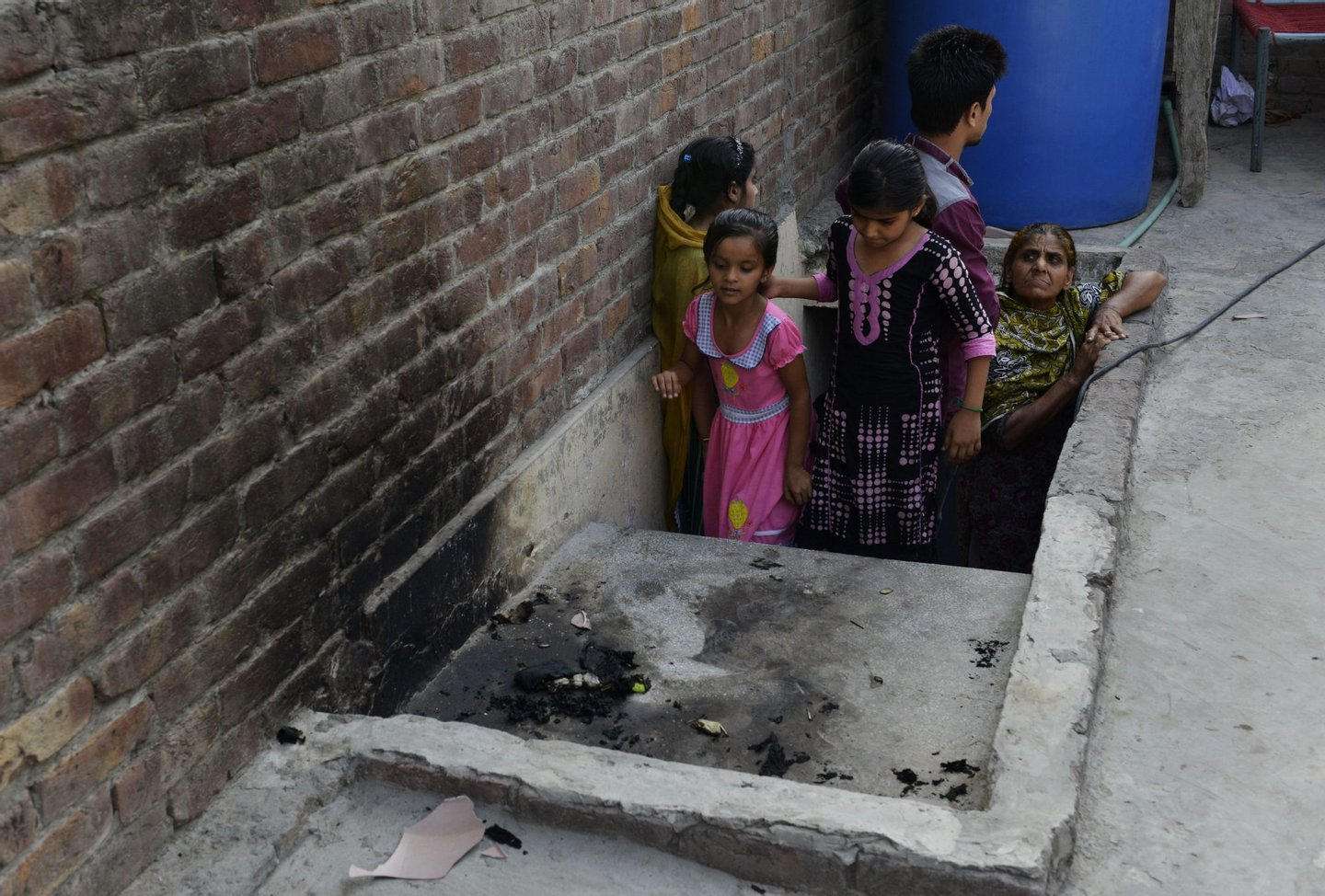 """Pakistani residents stand at the site where a teenager was burnt alive by her mother in Lahore on June 8, 2016. A Pakistani mother on June 8 burnt her 16-year-old daughter alive for marrying a man of her own choice, before running out her street to tell neighbours she had killed the teen for bringing shame to the family. It was the third so-called """"honour killing"""" in the South Asian country in as many months, and a rare example of the crime being carried out by a woman. / AFP / ARIF ALI (Photo credit should read ARIF ALI/AFP/Getty Images)"""