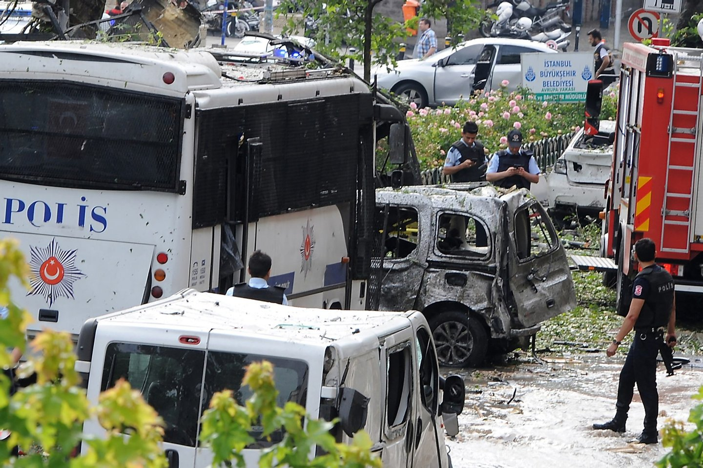 ALTERNATIVE CROP Police officers and rescuers inspect the site of a bomb attack that targeted a police bus in the Vezneciler district of Istanbul on June 7, 2016. A bomb attack targeted Turkish police in a central Istanbul district on June 7, 2016, leaving several people wounded, the state-run TRT television reported. / AFP / DOGAN NEWS AGENCY / STRINGER / Turkey OUT (Photo credit should read STRINGER/AFP/Getty Images)