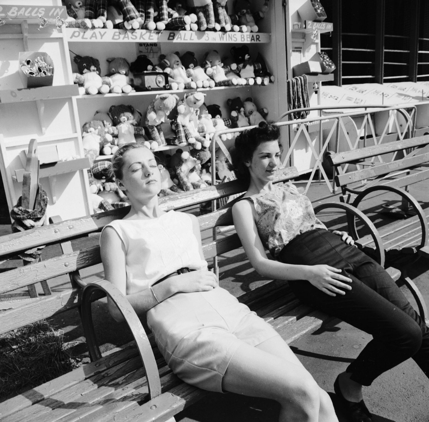 circa 1956: Two girls take a break from their summer jobs at the Palisades Amusement Park, New Jersey to bask in the noontime sun. (Photo by Sherman/Three Lions/Getty Images)