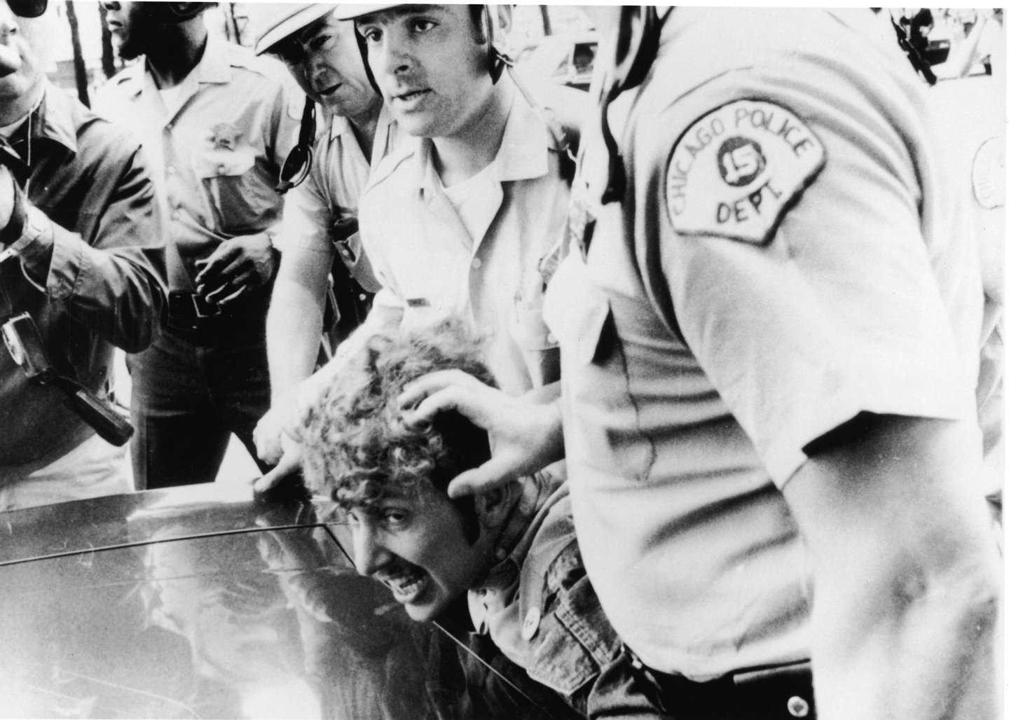 Officers from the Chicago Police Department push a protestor's head against the hood of a car as they restrain him after he climbed onto a wooden barricade near the Democratic headquarters of the 1968 Democratic National Convention and waved a Vietcong flag during anti-Vietnam War demonstrations, Chicago, Illinois, August 26, 1968. (Photo by APA/Getty Images)