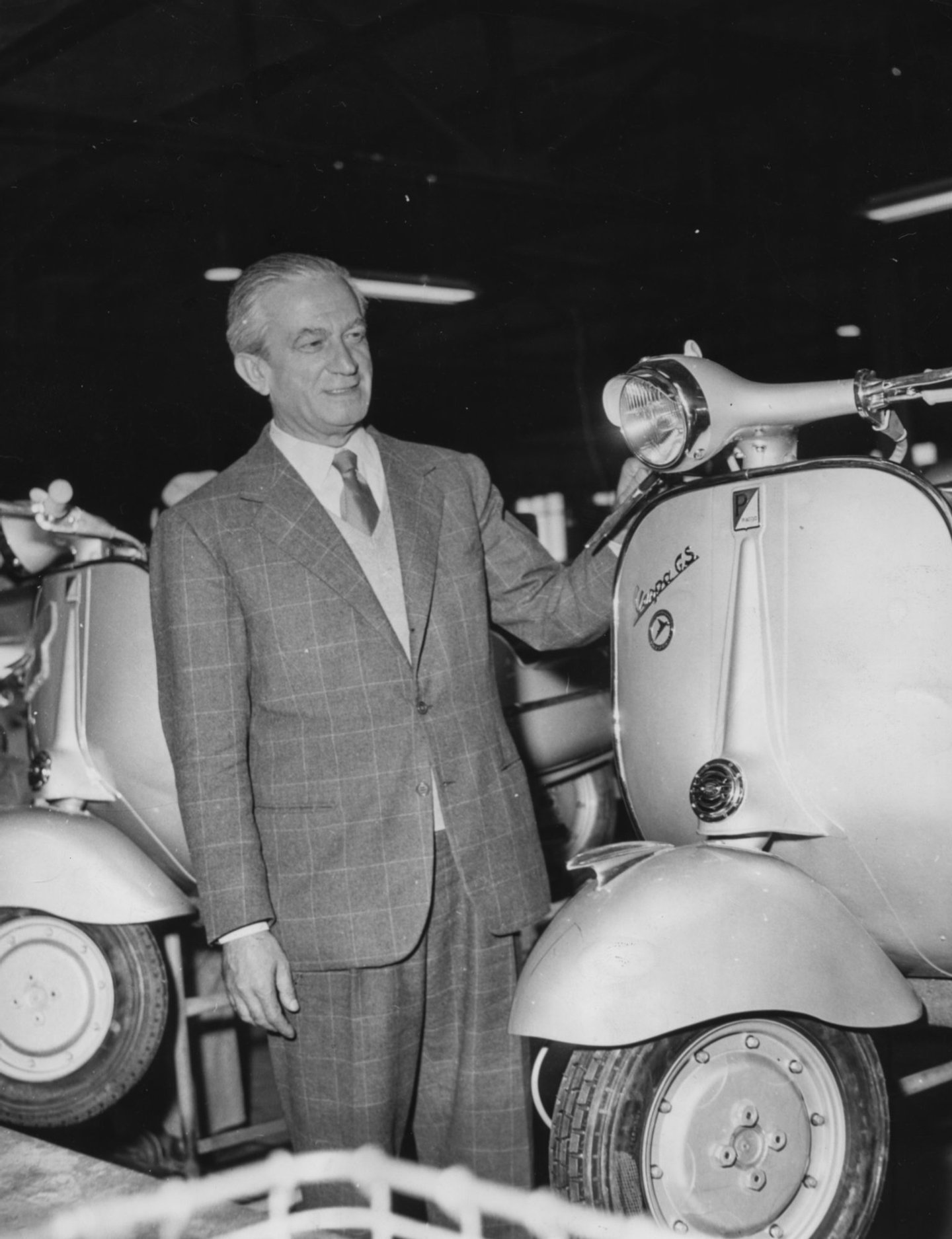 Italian industrialist Enrico Piaggio, manufacturer of Vespa scooters, pictured with one of the motor scooters at a Messerschmitt factory, Germany, October 2nd 1956. (Photo by Keystone Features/Hulton Archive/Getty Images)