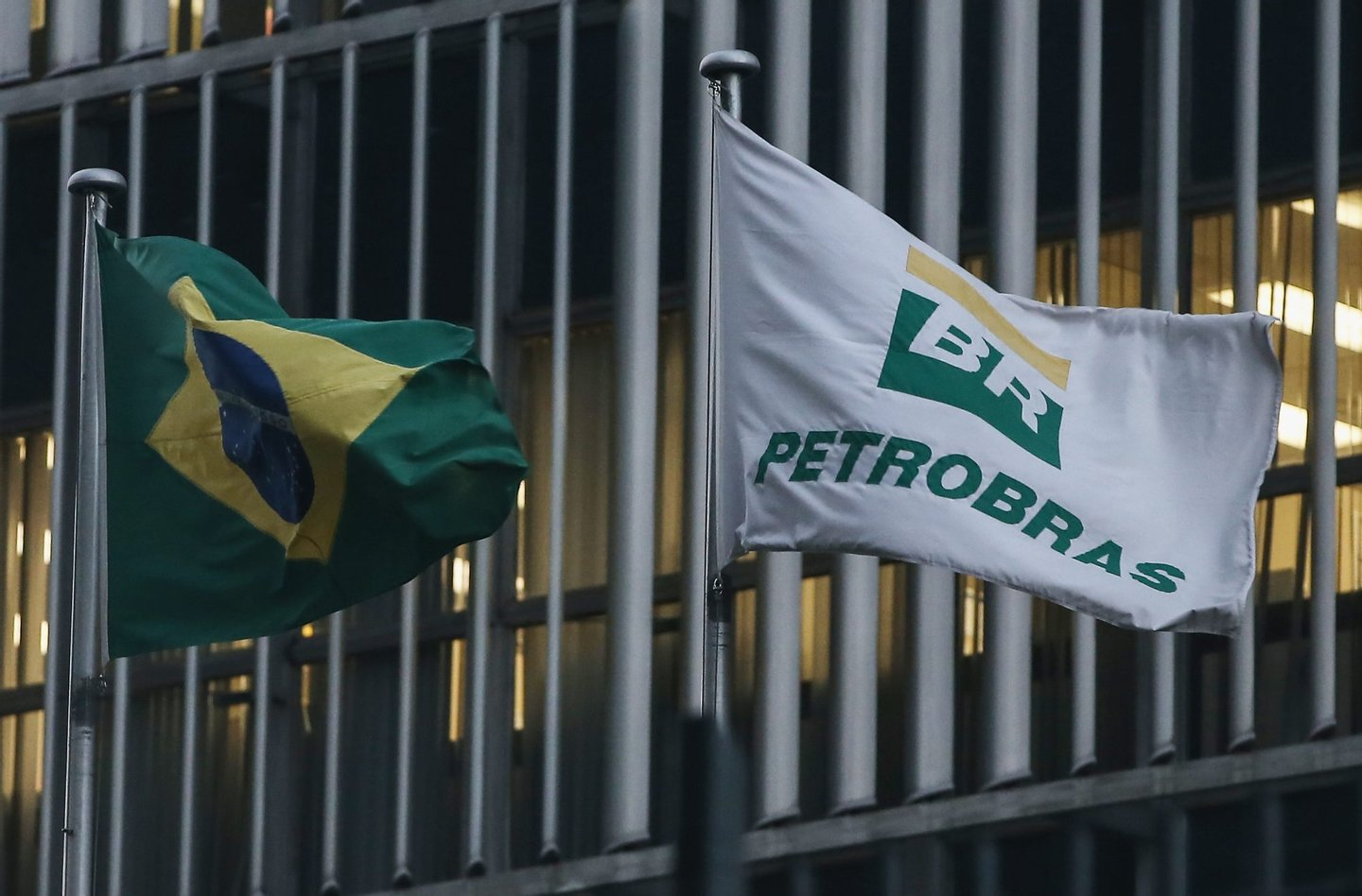 RIO DE JANEIRO, BRAZIL - APRIL 13: A Brazilian flag and a Petrobras flag fly in front of Petrobras headquarters on April 13, 2016 in Rio de Janeiro, Brazil. A massive corruption scandal at the state-owned oil company has sparked a political crisis in Brazil. President Dilma Rousseff, who has not been linked to the corruption scandal, was chairwoman of the Petrobras board from 2003-2010. President Rousseff is now facing impeachment with an initial vote set in the lower house of Congress for Sunday. (Photo by Mario Tama/Getty Images)