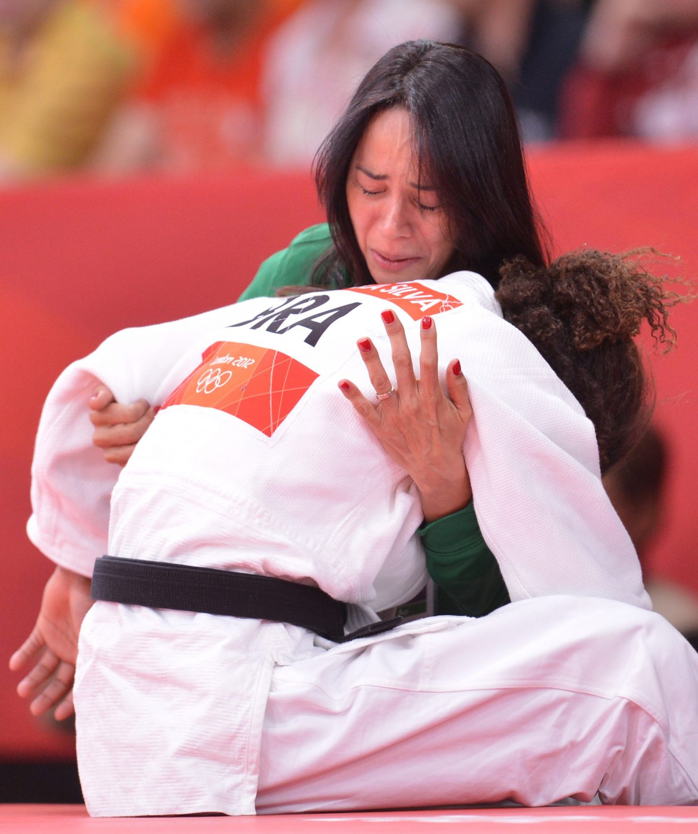 Brazil's Rafaela Silva commissarates with her coach Campos Rosicleia, after losing against Hungary's Hedvig Karakas during their women's -57kg judo contest match of the London 2012 Olympic Games on July 30, 2012 ExCel arena in London. AFP PHOTO / JOHANNES EISELE (Photo credit should read JOHANNES EISELE/AFP/GettyImages)