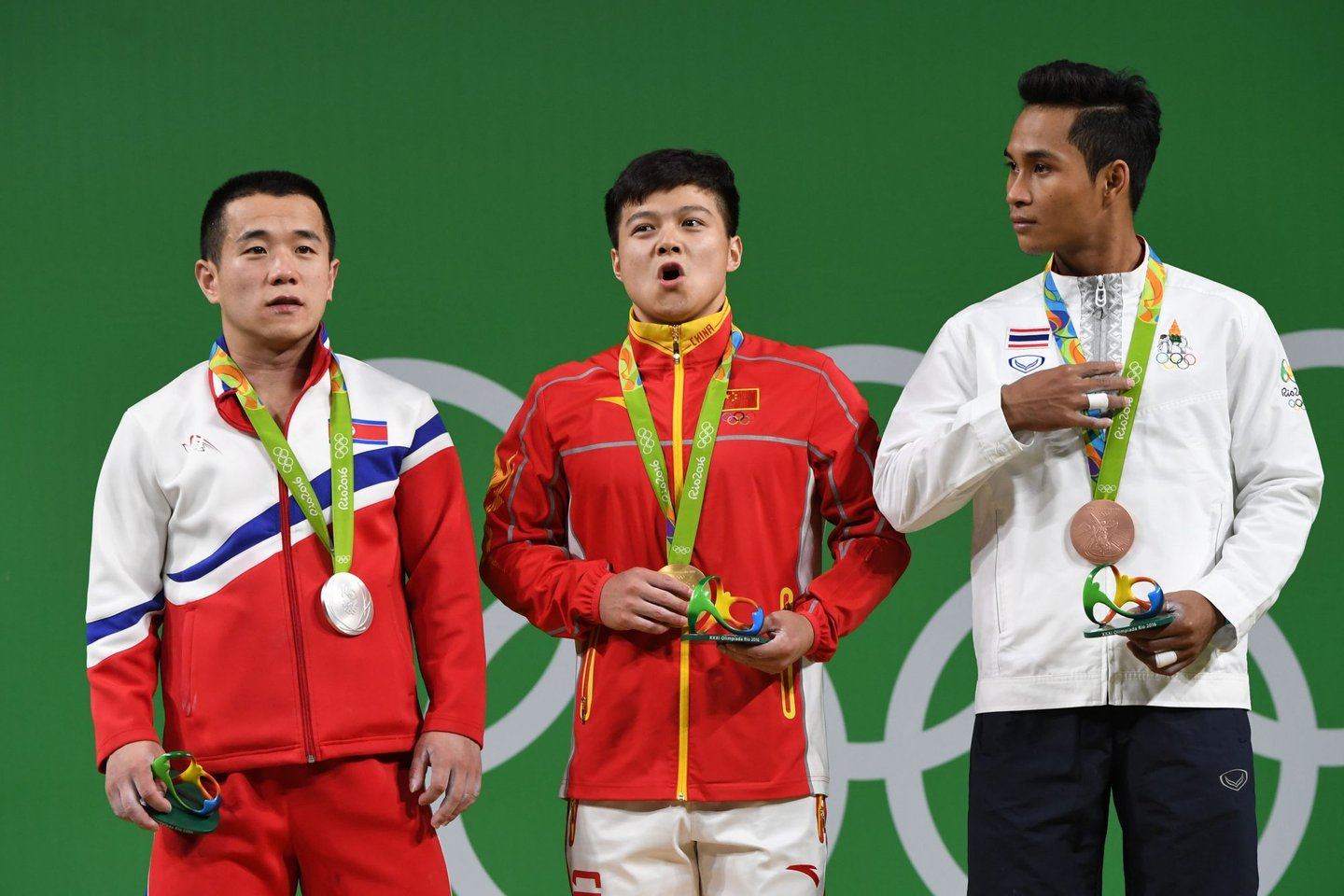 China's gold medallist Long Qingquan (C, North Korea's silver medallist Om Yun Chol (L) and Thailand's bronze medalist Sinphet Kruaithong pose with their medals on the podium during the men's 56kg weightlifting event at the Rio 2016 Olympic games in Rio de Janeiro on August 7, 2016. / AFP / GOH Chai Hin (Photo credit should read GOH CHAI HIN/AFP/Getty Images)