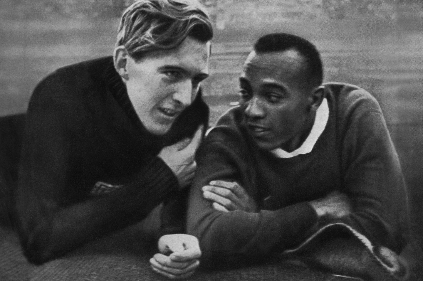 """US champion Jesse Owens (R) and German champion Luz Long (L) chat together on the Berlin stadium 01 August 1936 during the Olympic Games where Owens captured 4 gold medals, 100m, 200m, 4x100m and long jump. Luz, second of Owens, captured the long jump silver. Grandson of a slave and legendary athlete, """"Jesse"""" Owens established 6 world records in 1935. """"Jesse"""" Owens retained his 100m world record for 20 years and his long jump world record for 25 years (until 1960). (Photo credit should read CORR/AFP/Getty Images)"""