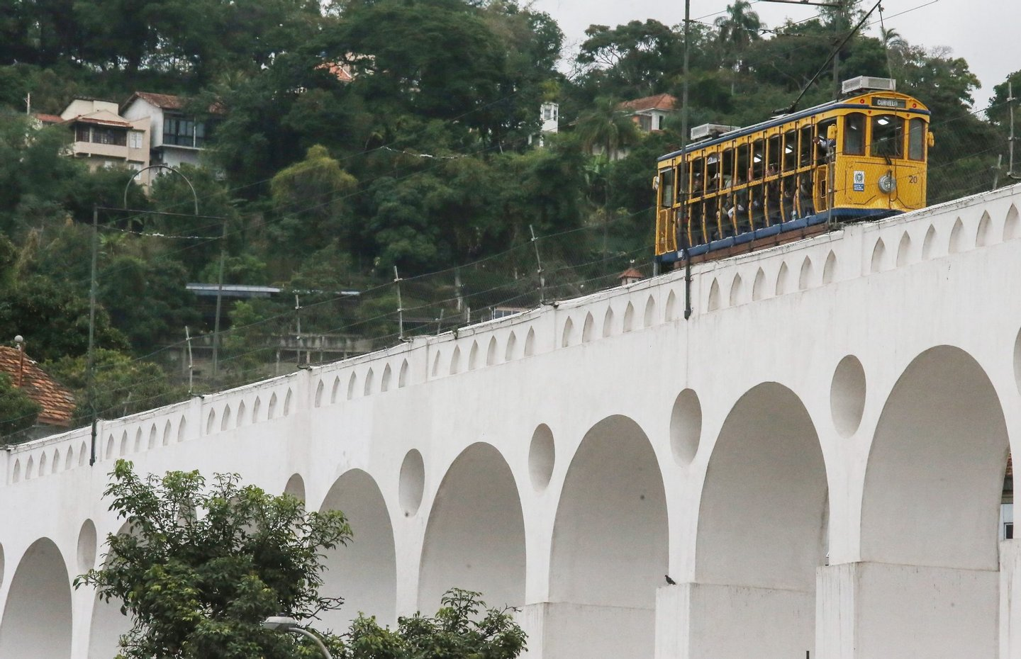 RIO DE JANEIRO, BRAZIL - JULY 27: Passengers ride across the Lapa Arches on the first day of pre-operations on the partially re-opened Santa Teresa tram line, or 'bonde', on July 27, 2015 in Rio de Janeiro, Brazil. The historic tram has been closed since a derailing accident in 2011 which left six dead and fifty injured. The first stretch to re-open covers about one kilometer of the scenic ten kilometer route. It has been operating since the late 19th century and is one of the oldest electric streetcar lines in Latin America. Rio is working on various transportation upgrade projects ahead of the games. August 5 marks the one-year mark to the start of the Rio 2016 Olympic Games. (Photo by Mario Tama/Getty Images)