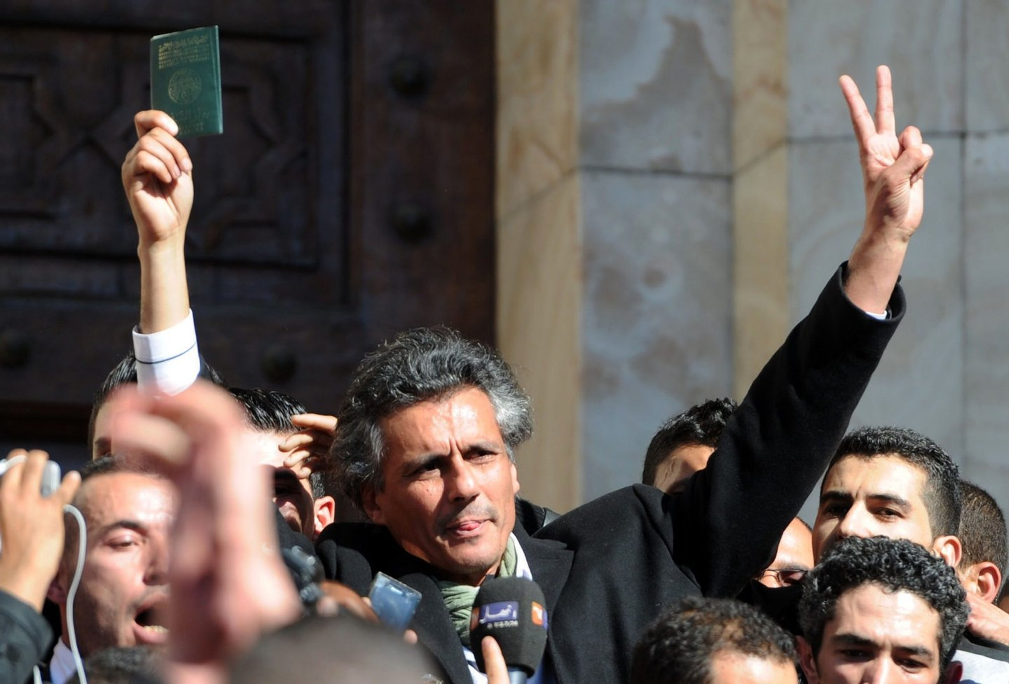 Rachid Nekkaz, who wanted to be candidate but couldn't register for Algeria's April 17 presidential election, flashes the sign of victory during a protest in his support in Algiers on March 8, 2014. Nekkaz said his candidature documents were stolen before he submits them at the constitutional council. AFP PHOTO / FAROUK BATICHE (Photo credit should read FAROUK BATICHE/AFP/Getty Images)