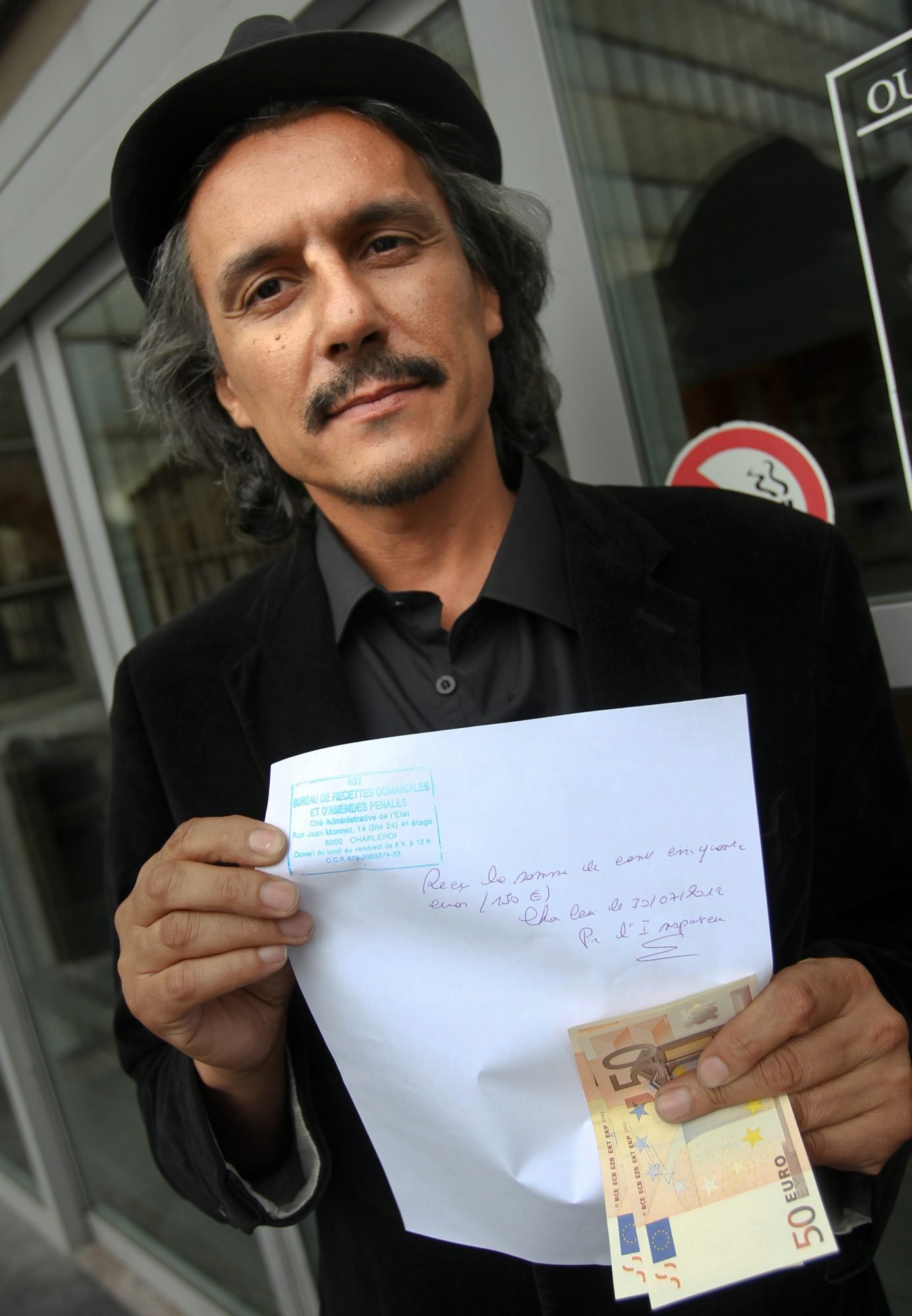 French businessman and 2007 presidential candidate Rachid Nekkaz poses with a fine payment receipt and bills as he walks out of a police station in Charleroi after paying a fine which was handed to a woman wearing a full-veil niqab, in Charleroi, on July 30, 2012. After the Belgium government approved a controversial 'anti-burqa' law similar to the one in France, Nekkaz announced he would pay any fine for women who want to wear the full islamic veil 'burqa' or 'niqab' in Belgium or France. AFP PHOTO / BELGA / VIRGINIE LEFOUR ***BELGIUM OUT*** (Photo credit should read VIRGINIE LEFOUR/AFP/GettyImages)