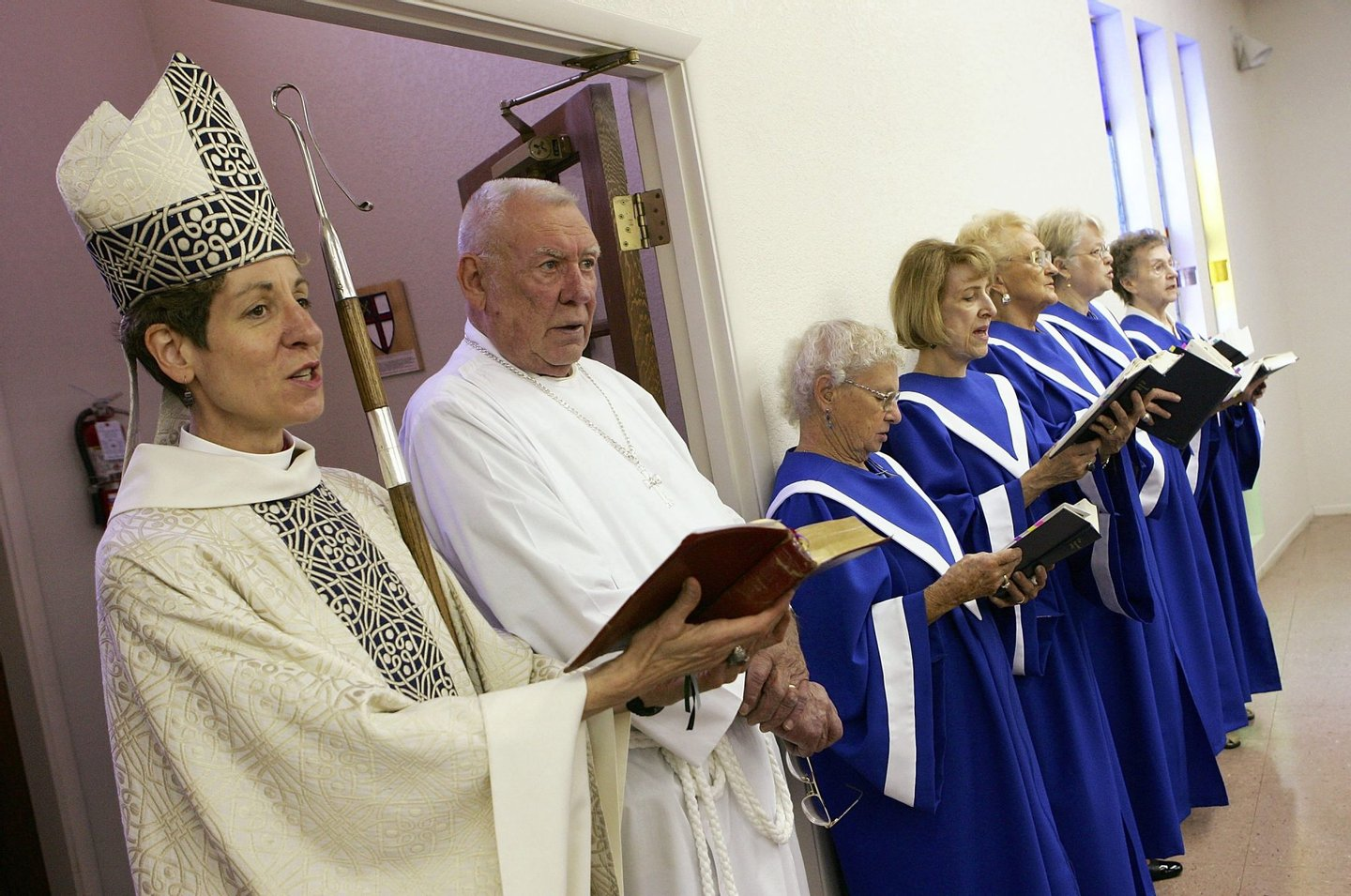 BULLHEAD CITY, AZ - JULY 02: Bishop Katharine Jefferts Schori (L) and chalice bearer Dick Studeny (2nd L) sing during the recessional of a service at The Episcopal Church of the Holy Spirit July 2, 2006 in Bullhead City, Arizona. Schori is the first female presiding bishop-elect for the Episcopal Church. (Photo by Ethan Miller/Getty Images)