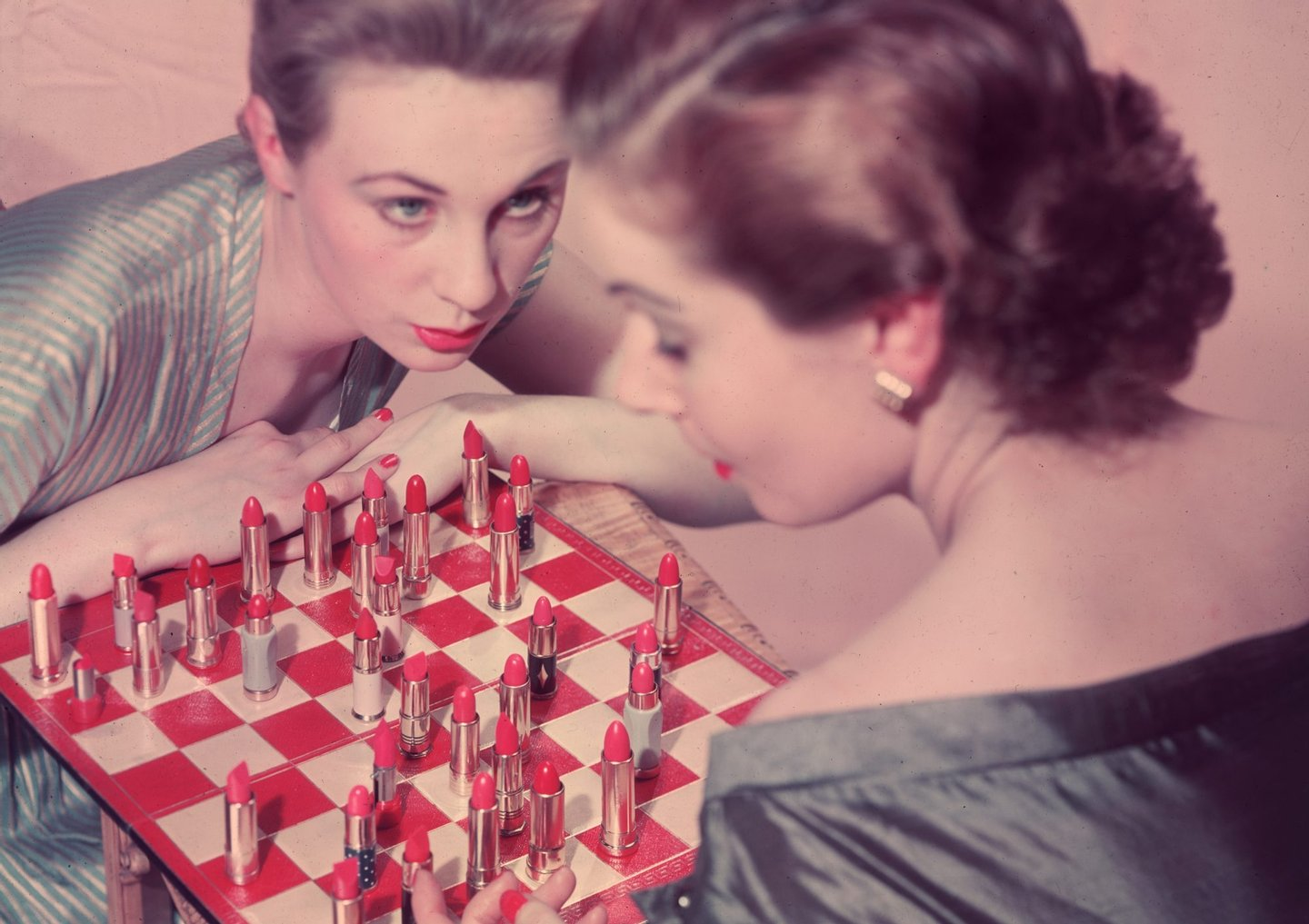 circa 1955: Two women playing an unusual game of chess, with lipstick instead of chess pieces. (Photo by Chaloner Woods/Getty Images)