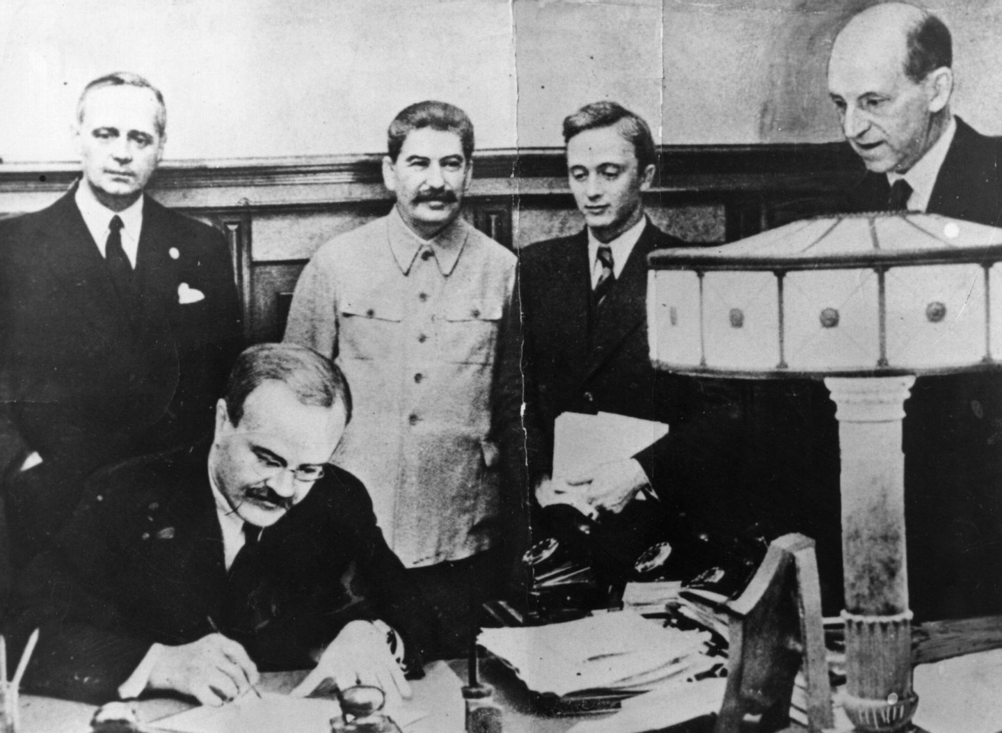 23rd August 1939: Vyacheslav Molotov, Russian Foreign Minister, signs the non-aggression pact negotiated between Soviet Russia and Germany, at the Kremlin, Moscow. Standing behind him is his German counterpart Joachim von Ribbentrop (left), and Joseph Stalin (centre). (Photo by Keystone/Getty Images)