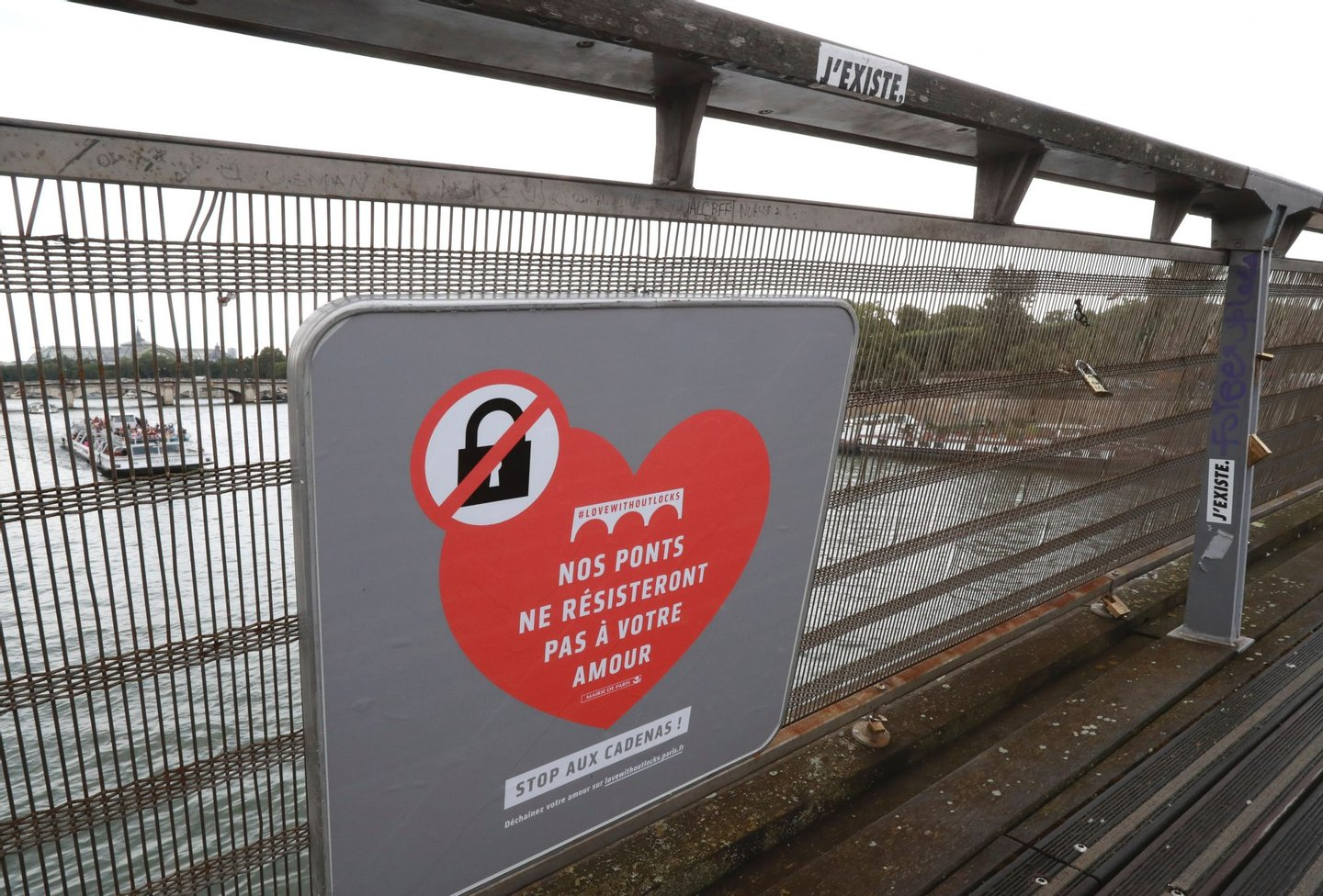 """A placard reading """"our bridges won't resist your love"""" is seen on the footbridge of Leopold-Sedar-Senghor in Paris, on August 4, 2016. Love may know no bounds, but Paris intends to instill some: authorities are going to take a tougher line with swooning couples attaching """"love-locks"""" to city bridges as a sign of their undying devotion. In June last year authorities removed hundreds of thousands of such padlocks from the city bridges, notably the Pont des Arts which had a section collapse under the weight of the locks. / AFP / JACQUES DEMARTHON (Photo credit should read JACQUES DEMARTHON/AFP/Getty Images)"""