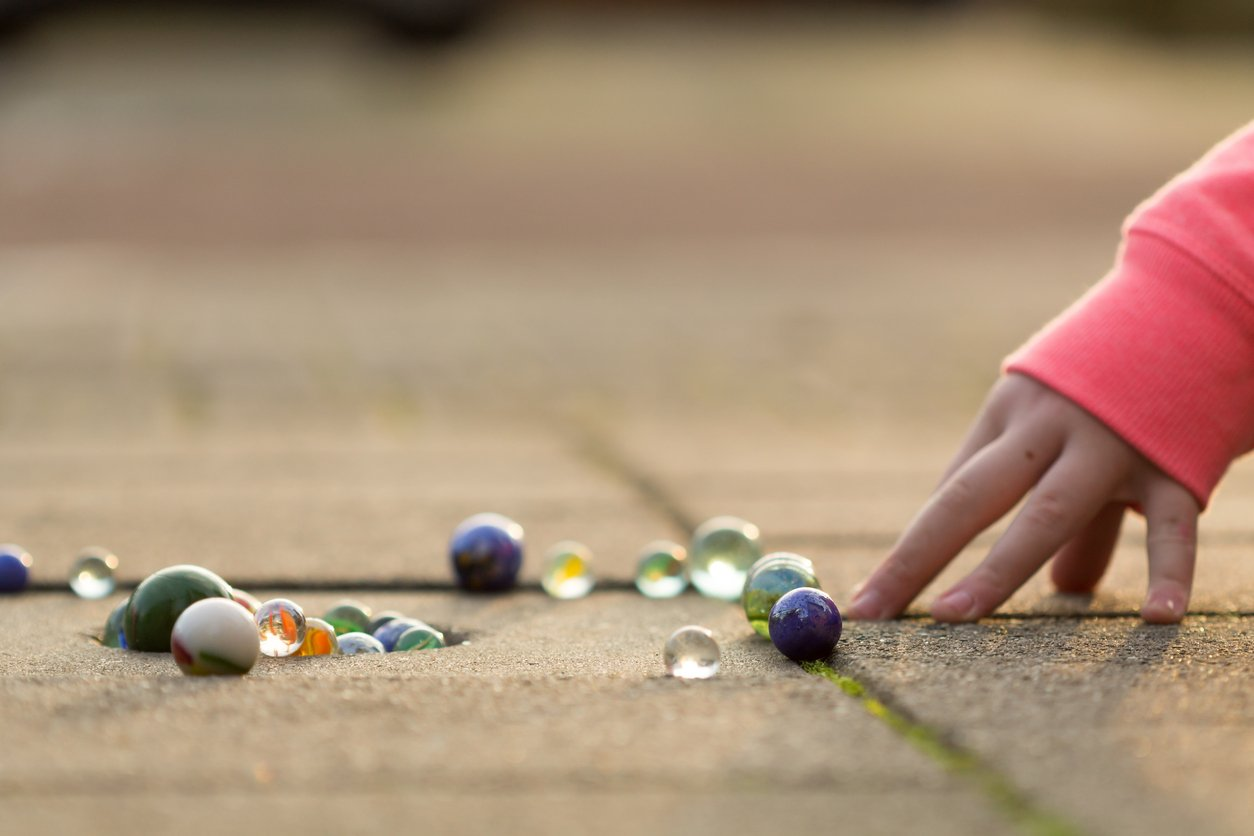 Crystal, Girls, Cement, Play, Marbles, Child, Playing, Sidewalk, Fun, Caucasian Ethnicity, One Person, Variation, Happiness, Circle, Sphere, Pink Color, Colors, Glass - Material, Shiny, Lifestyles, Childhood, Human Hand, People, Sunlight, Land, Street, Toy, Leisure Games,