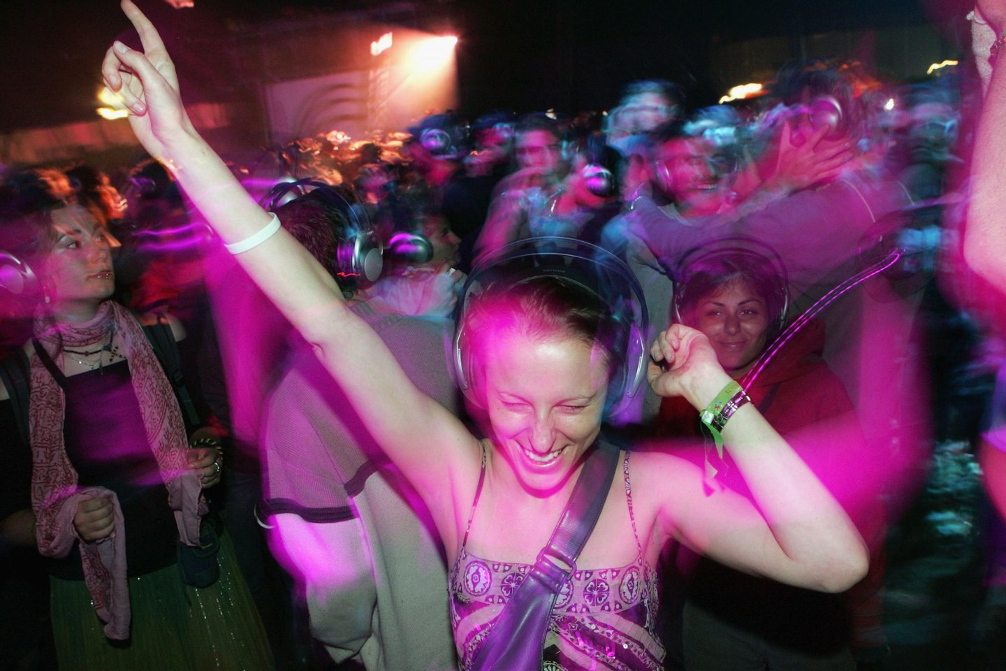 GLASTONBURY, ENGLAND - JUNE 25: A reveller enjoys the silent all-night disco in the Dance Tent on the second day of the Glastonbury Music Festival 2005 at Worthy Farm, Pilton on June 25, 2005 in Somerset, England. The headphones cost ?75, have two channels and over a 1000 were given out. The festival runs until June 26. (Photo by Matt Cardy/Getty Images) *** Local Caption ***